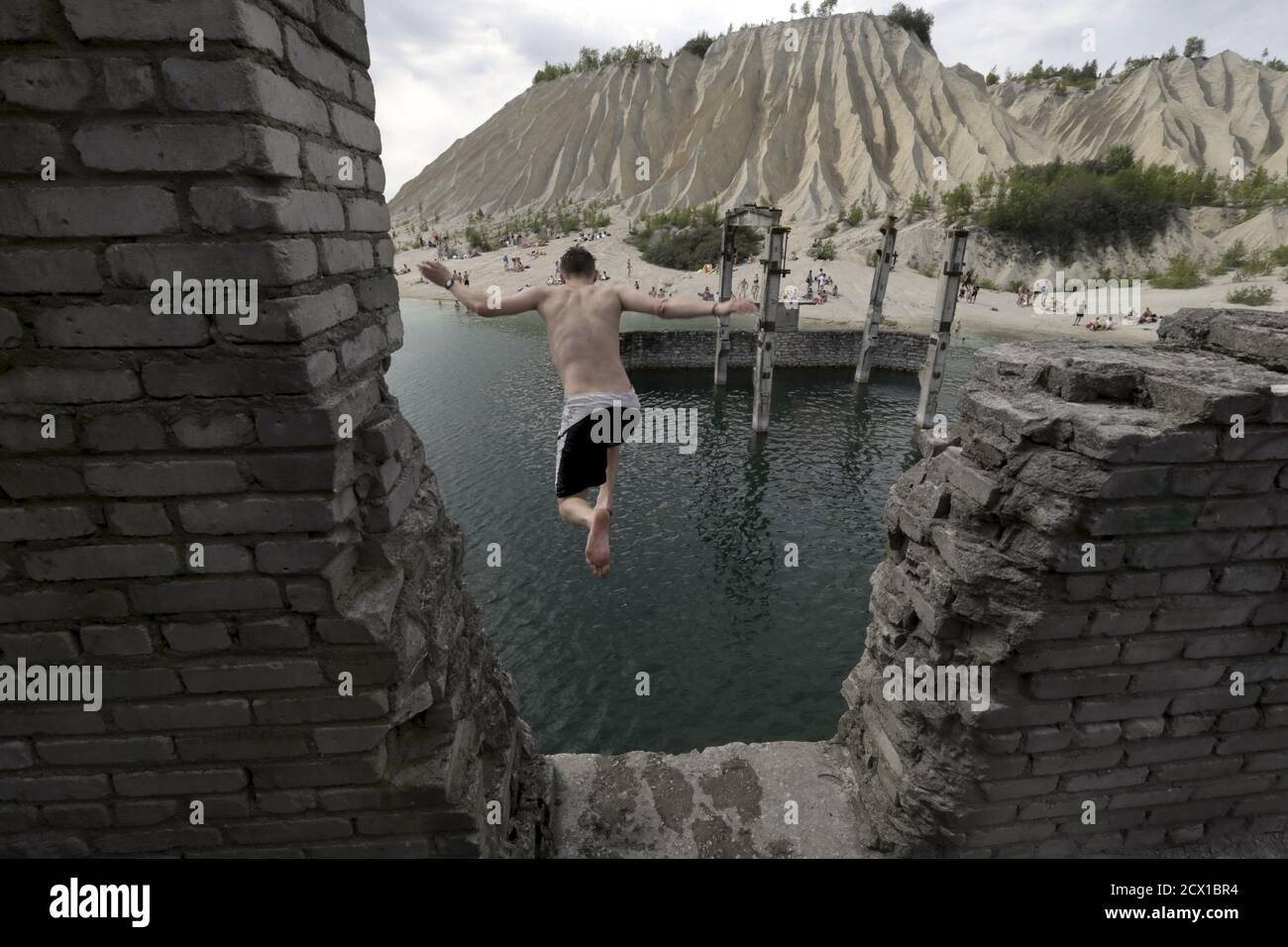 A man jumps into water from the roof of the abandoned Soviet time prison in Rummu quarry, Estonia, during hot weather July 4, 2015. During the Soviet time, Rummu quarry was used as a mining site for Vasalemma marble and most of the workforce came from among the detainees of Murru prison. When the prison closed after 1991, pumps that once kept the quarry and the prison dry were shut down, causing water to fill the quarry. It has become an unofficial and unguarded swimming and diving spot, attracting locals and tourists. REUTERS/Ints Kalnins Stock Photo