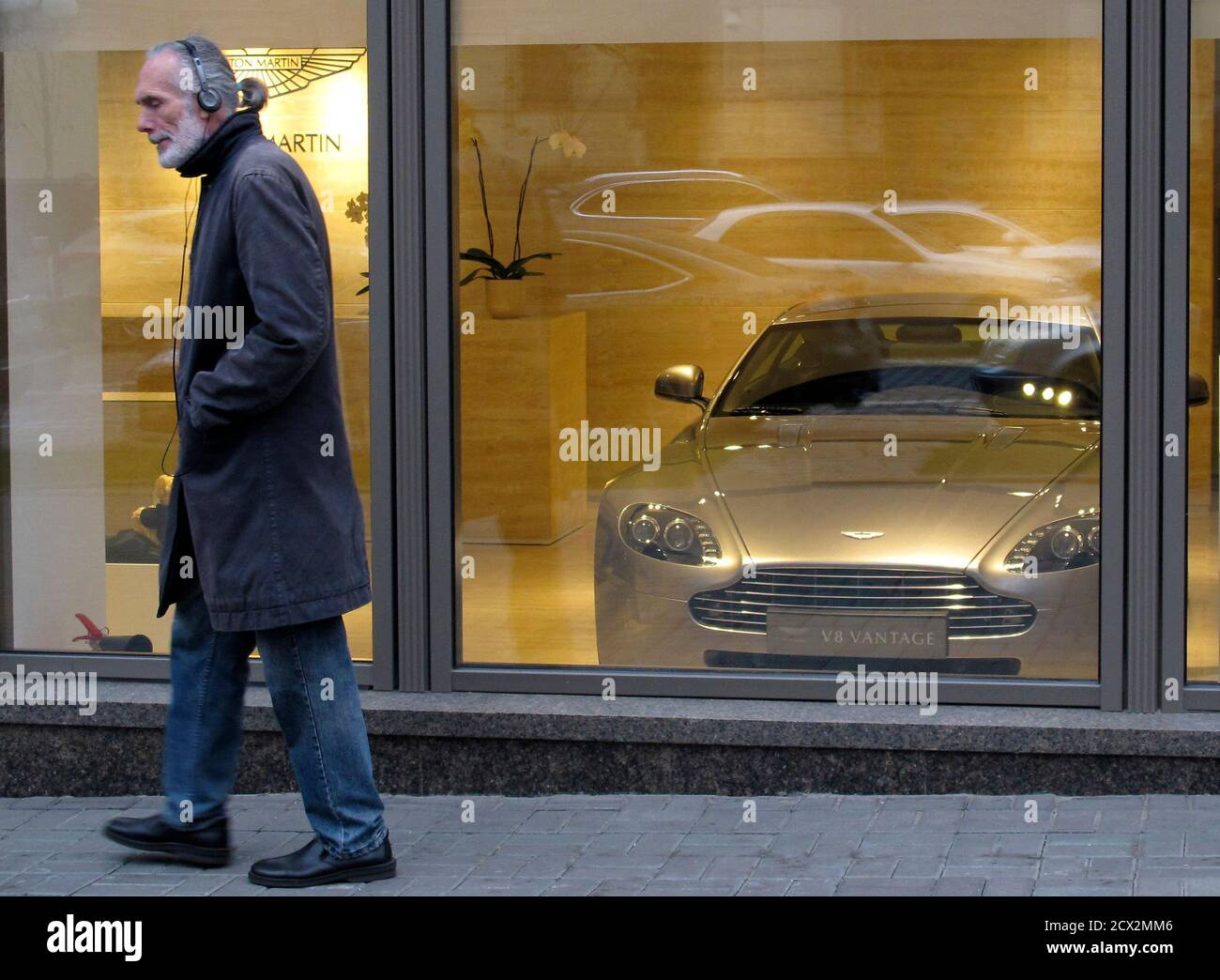 A Man Passes By A Shop Window With A Aston Martin V8 Vantage On Display In Kiev October 31 2011 Reuters Gleb Garanich Ukraine Tags Society Transport Business Stock Photo Alamy