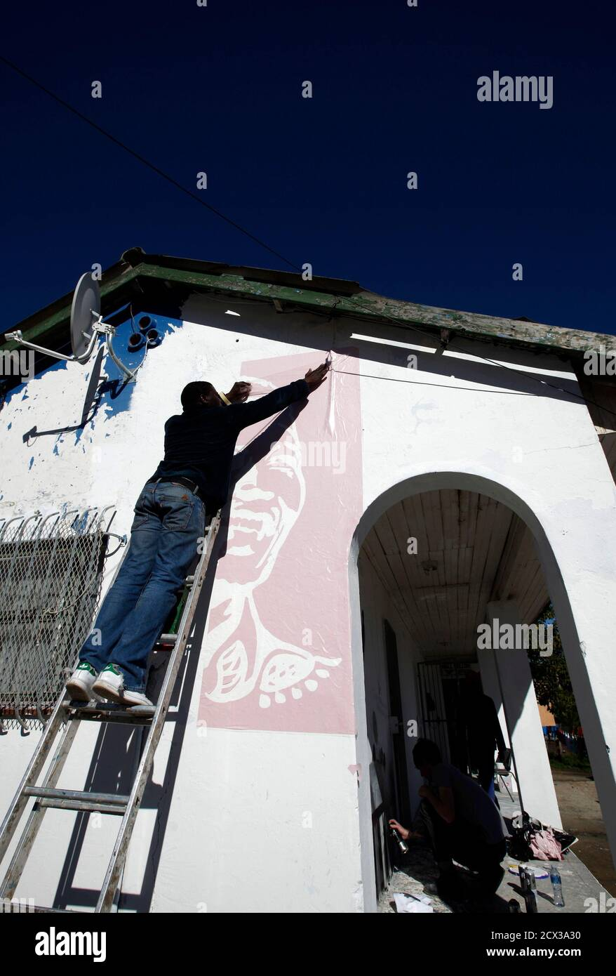 A volunteer paints a mural depicting the life of former President Nelson Mandela at a library in Cape Town's Imizamo yethu township, July 18, 2012. Thousands of South Africans heeded the call to offer 67 minutes of their time to help build communities as part of celebrations of Mandela's 94 birthday today.  REUTERS/Mike Hutchings (SOUTH AFRICA - Tags: POLITICS ANNIVERSARY SOCIETY) Stock Photo