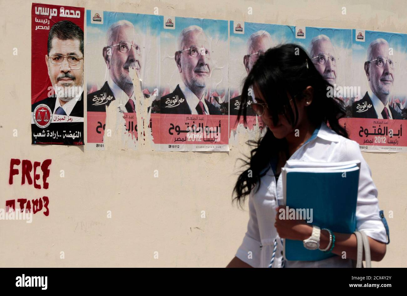 A woman walks past campaign posters of Mohamed Mursi (L), presidential candidate and head of the Muslim Brotherhood's political party and Abdel Moneim Abu El Fotouh, presidential candidate and a former leader of the Muslim Brotherhood, in Cairo May 7, 2012. Voting starts on May 23-24 in the election to choose a new president after Hosni Mubarak was turfed out of office last year. REUTERS/Amr Abdallah Dalsh  (EGYPT - Tags: POLITICS ELECTIONS) Stock Photo