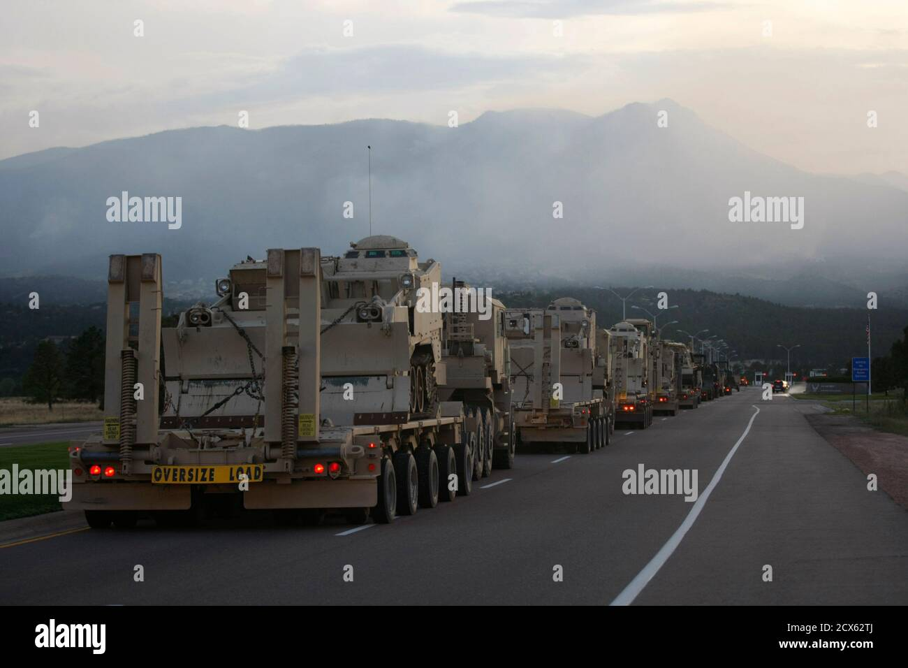 A long line of U.S. Army vehicles and equipment from Ft. Carson arrives at the U.S. Air Force Academy in Colorado Springs, Colorado with the Waldo Canyon fire smoke seen over the base June 27, 2012. Firefighters struggled on Wednesday to beat back the fiercely aggressive wildfire raging at the edge of Colorado Springs that has forced at least 35,000 people from their homes and was nipping at the edges of the academy. The convoy included many large earth-moving machines, troops and supplies for the army to use to help defend the academy from the fire. REUTERS/Rick Wilking (UNITED STATES - Tags: Stock Photo