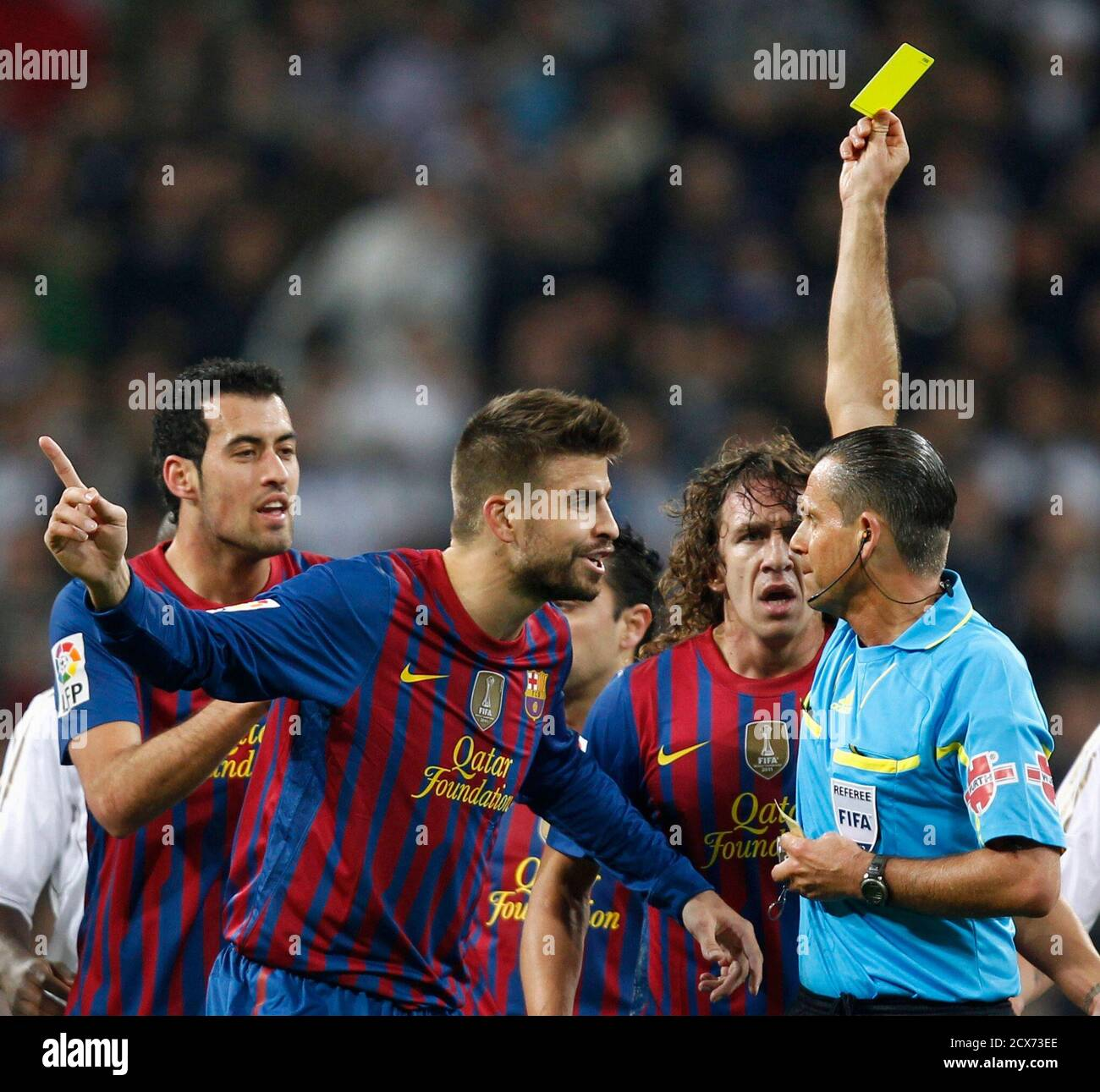 """Referee Cesar Muniz (R) shows the yellow card to Barcelona's Gerard Pique after jumping for the ball with Real Madrid's Pepe (not pictured), during their Spanish King's Cup quarter-final first leg """"El Clasico"""" soccer match at the Santiago Bernabeu stadium in Madrid, January 18, 2012.  REUTERS/Sergio Perez (SPAIN - Tags: SPORT SOCCER) Stock Photo"""
