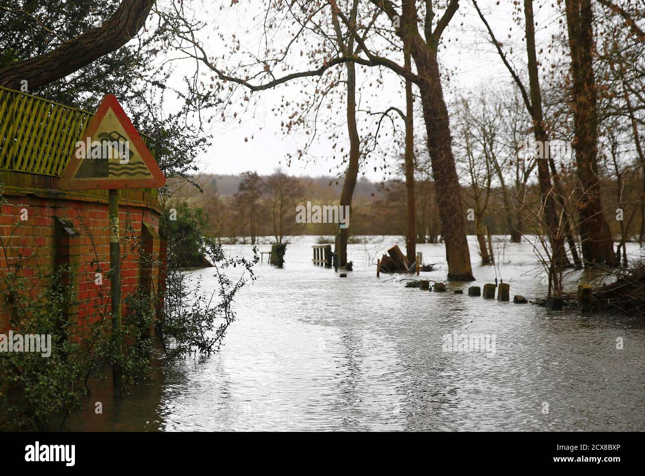 A danger sign is seen as water from the Thames River floods the village of Medmenham, southern England February 12, 2014. REUTERS/Eddie Keogh (BRITAIN - Tags: ENVIRONMENT DISASTER) Stock Photo