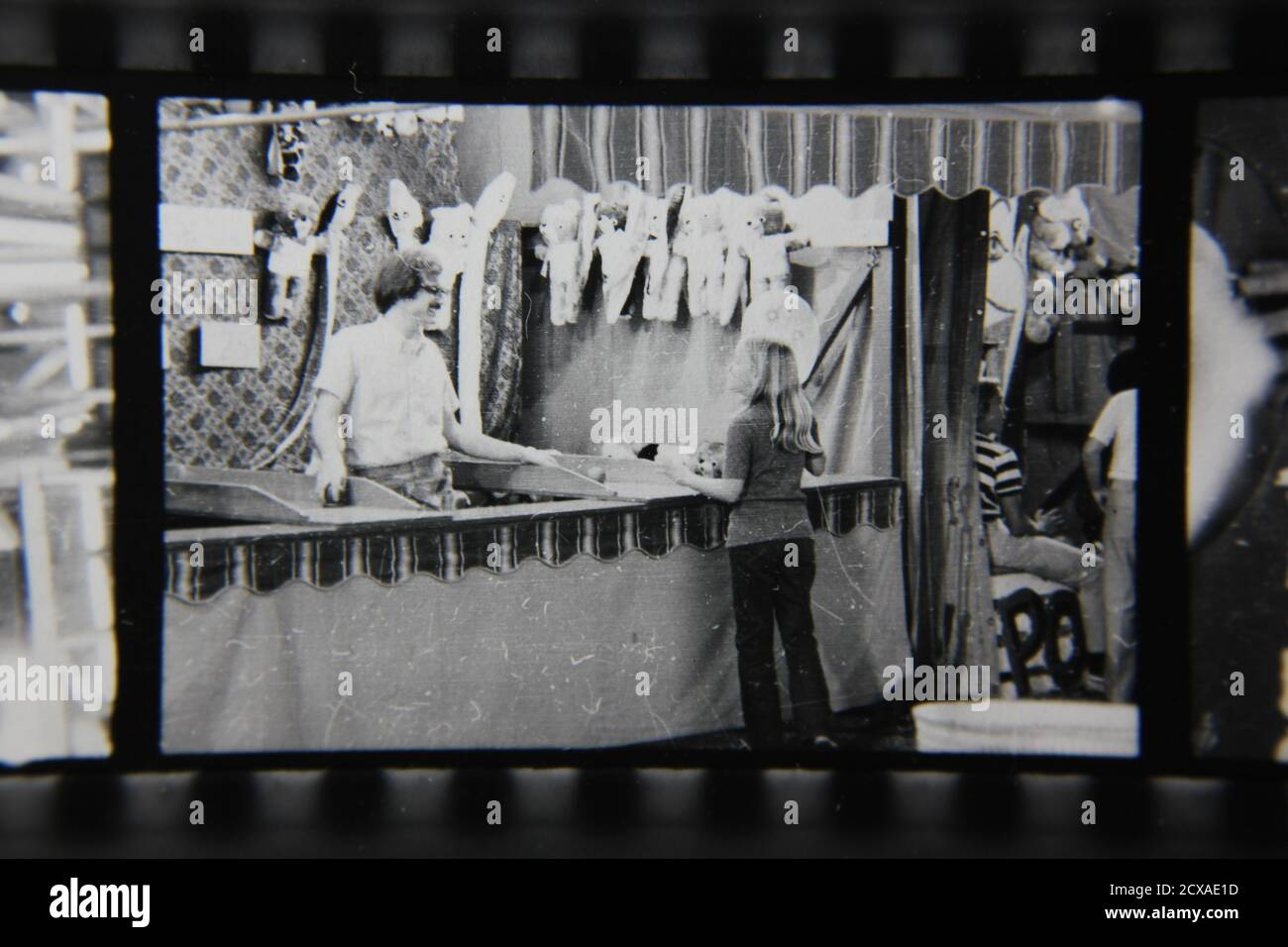 Fine 1970s vintage black and white photography of a regular guy manning a carnival game booth at a carnival street fair. Stock Photo