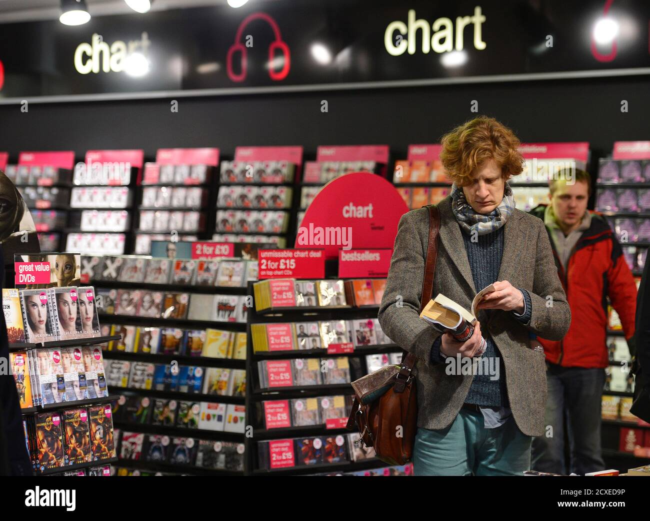 A customer looks at a book in an HMV shop in central London, January 15, 2013. HMV, the 92-year-old British music retailer seeking protection from creditors, is unlikely to have much of a future beyond a rump of stores and the internet, if other recent retail failures are any guide.    REUTERS/Paul Hackett (BRITAIN - Tags: BUSINESS MEDIA ENTERTAINMENT) Stock Photo