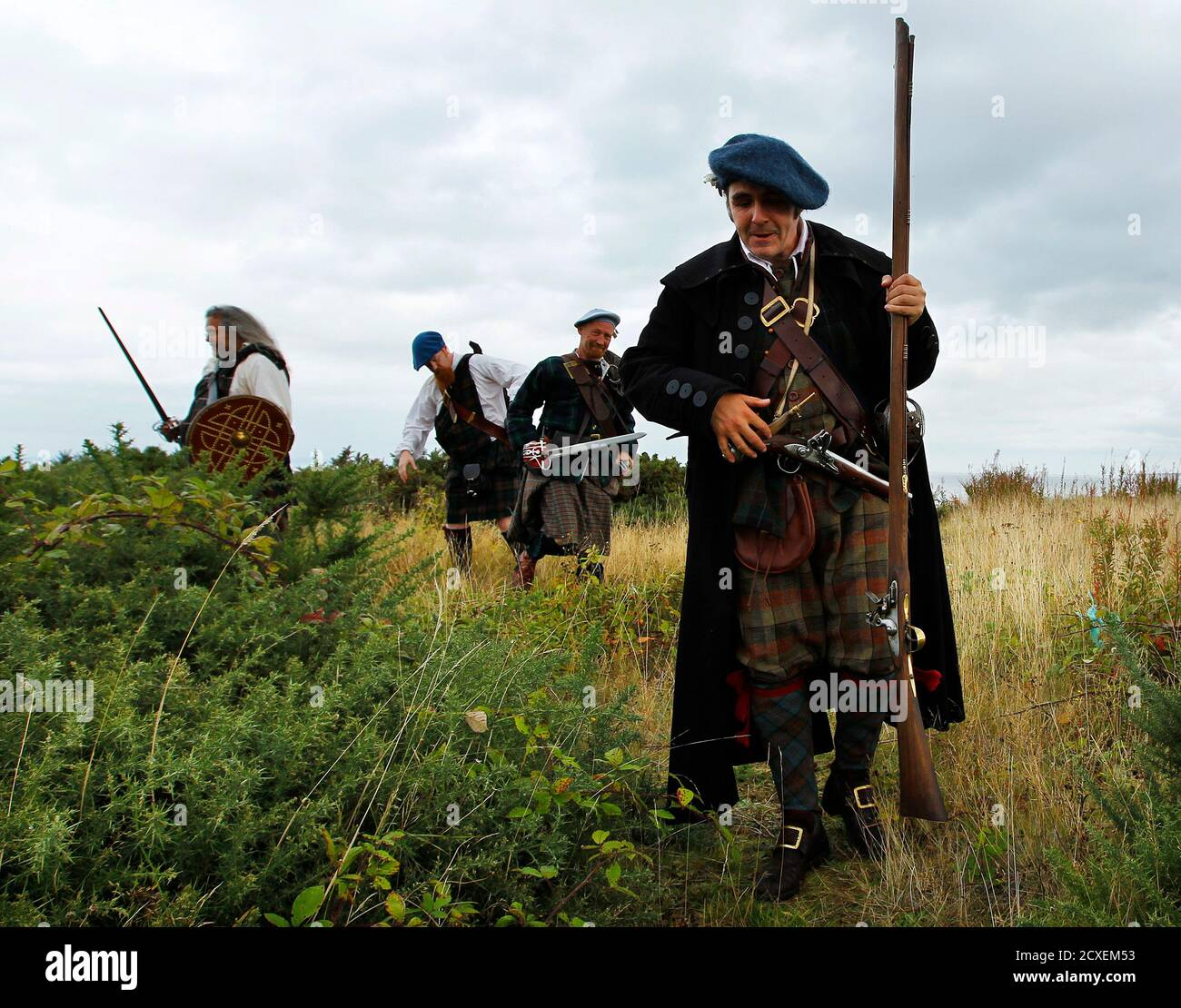 Jacobite Highlander re-enactors walk away after posing for photographers during a media event for the forthcoming Battle of Prestonpans re-enactment, in Prestonpans, East Lothian in Scotland September 21, 2010. The actors were in Prestonpans for a photocall to publicise this weekend's re-enactment of the Battle of Prestonpans from 1745 which saw Bonnie Prince Charlie and his army of Jacobite Highlanders defeat the British government troops lead by Sir John Cope. REUTERS/David Moir (BRITAIN - Tags: ENTERTAINMENT) Stock Photo