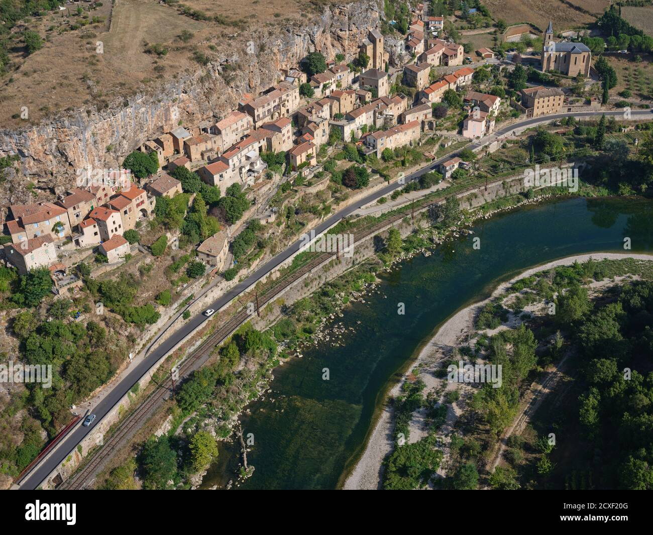 AERIAL VIEW. Picturesque village situated at the foot of a cliff and overlooking the Tarn River. Peyre, Comprégnac, Aveyron, Occitanie, France. Stock Photo