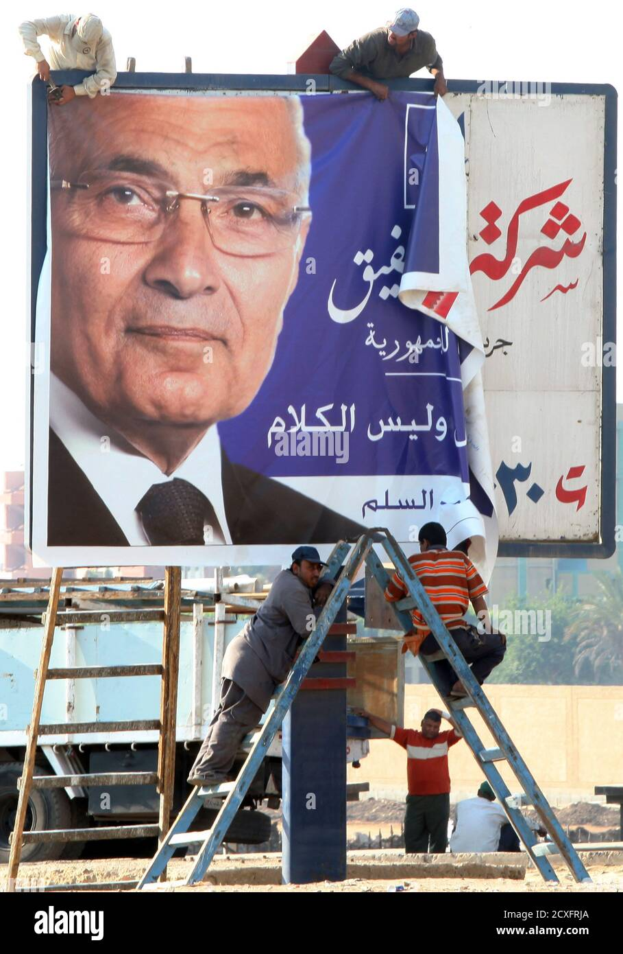 Egyptian workers hang up a campaign poster of presidential candidate and former prime minister Ahmed Shafiq in Cairo May 7, 2012. Voting starts on May 23-24 in the election to choose a new president after Hosni Mubarak was turfed out of office last year. REUTERS/Amr Abdallah Dalsh  (EGYPT - Tags: POLITICS ELECTIONS) Stock Photo