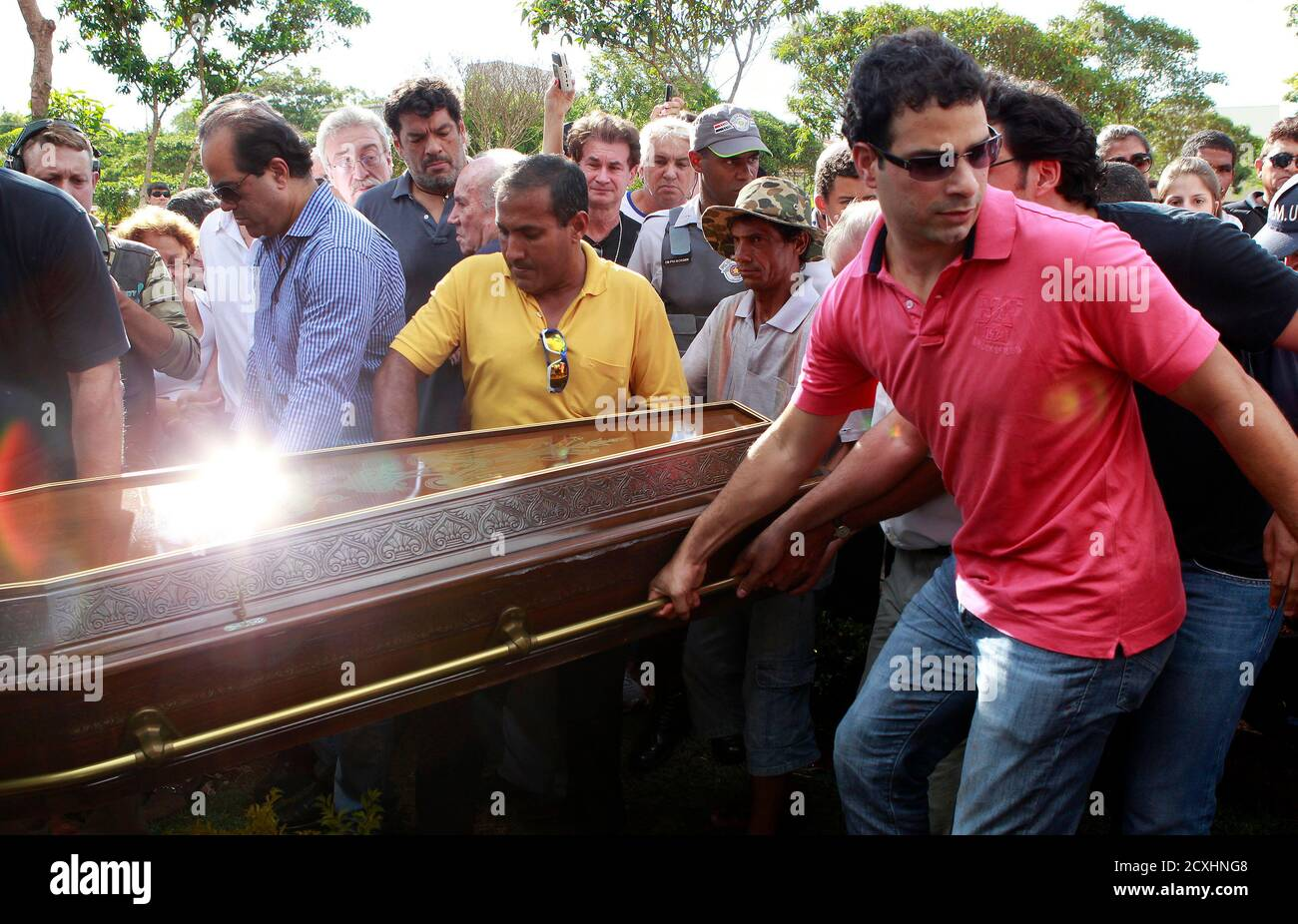 Gustavo Oliveira (R) carries the coffin of his father, Brazil's 1982 World Cup captain Socrates, during his funeral ceremony in Ribeirao Preto December 4, 2011. Socrates, the 'Golden Heel' renowned as one of the great playmakers of his generation, died in hospital on Sunday of septic shock at the age of 57, his doctors said in a statement.   REUTERS/Paulo Whitaker  (BRAZIL - Tags: SPORT SOCCER OBITUARY) Stock Photo