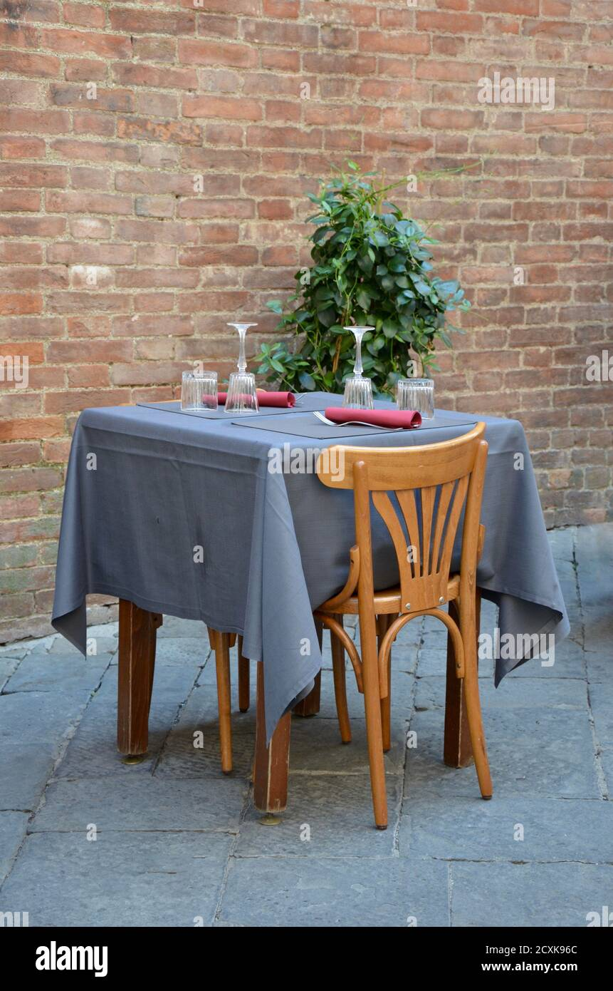 Empty Table With Two Wooden Vintage Chairs In An Outdoor Restaurant In Tuscany Italy Stone Wall Behind Stock Photo Alamy