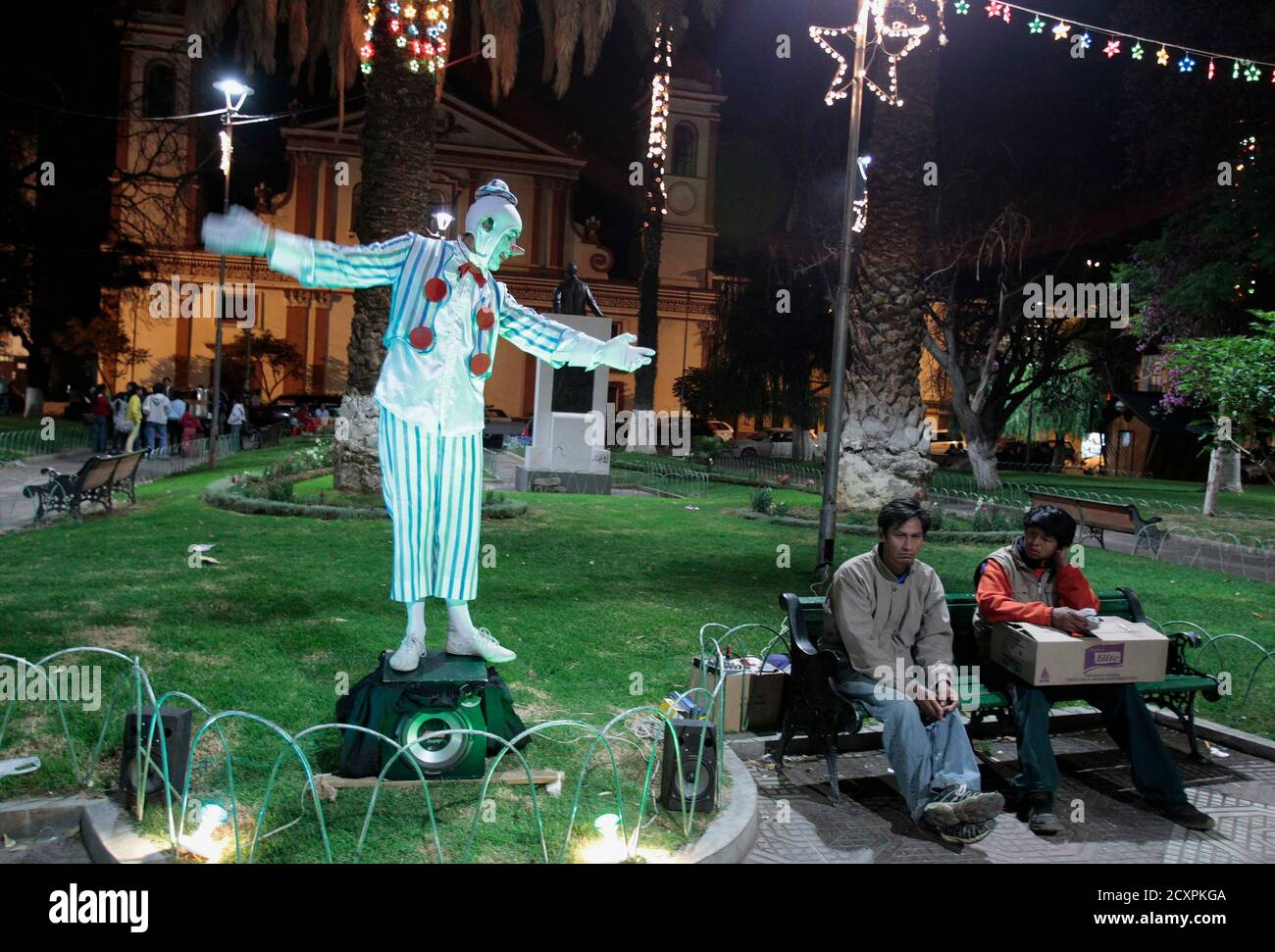 Men sit on a bench as a sidewalk mime artist performs at Colon Square in Cochabamba December 12, 2011. REUTERS/David Mercado (BOLIVIA - Tags: SOCIETY) Stock Photo