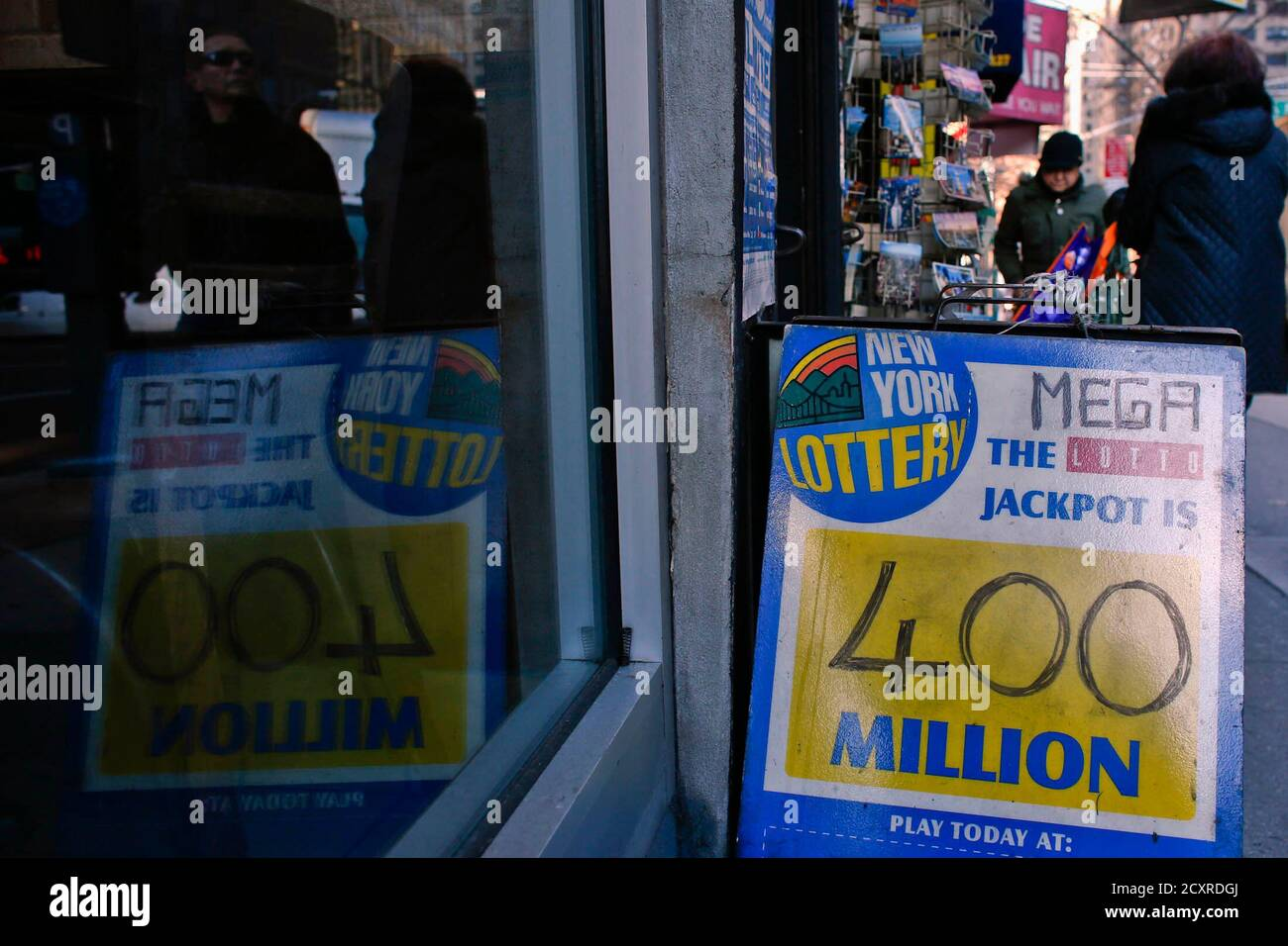 People Walk Next To A Mega Millions Poster After The Lottery Grand Prize Rose To 400