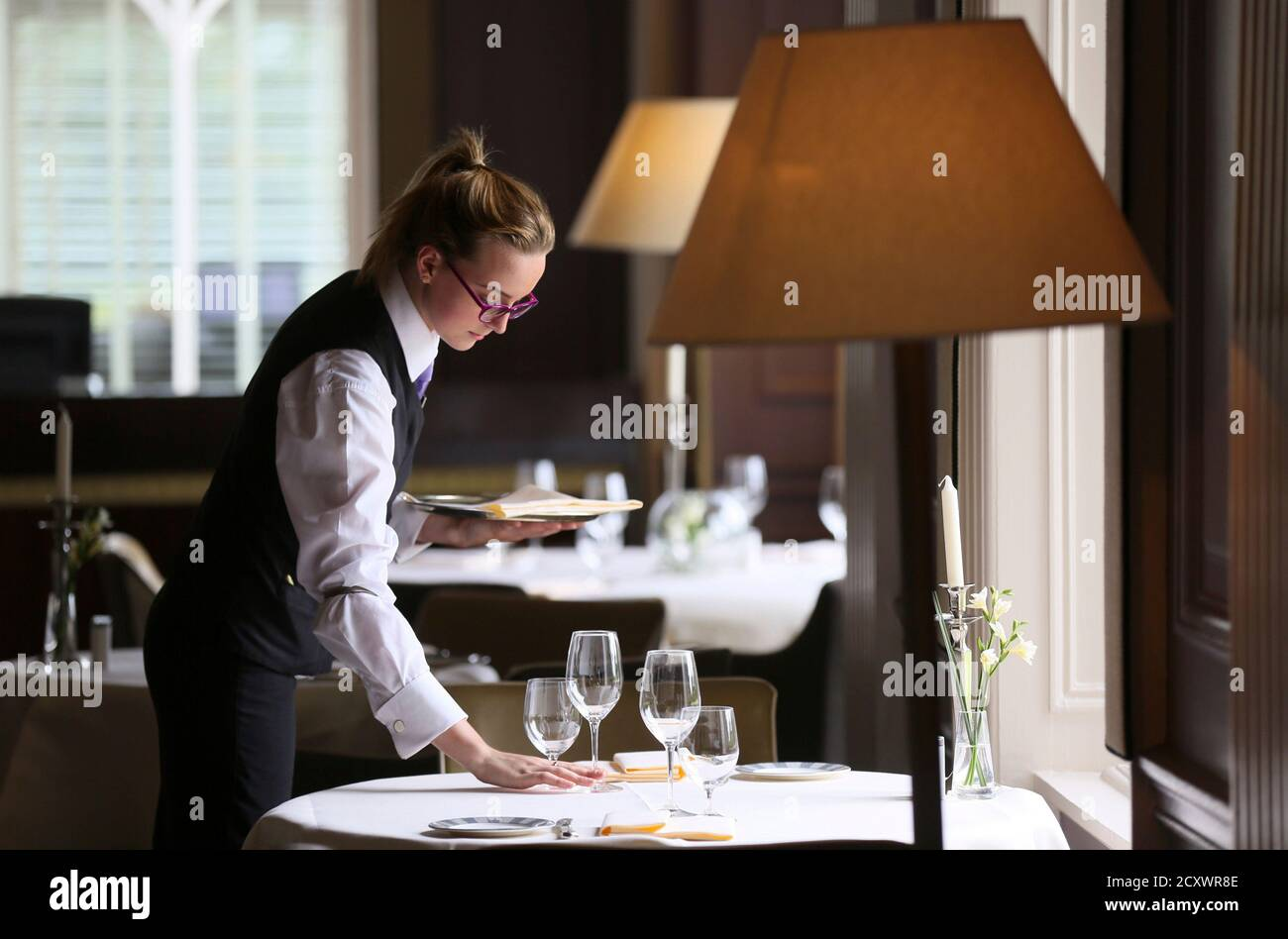 Commis de Rang Amy Connolly poses for a photograph as she sets the table in the Strathearn Restaurant at the Gleneagles Hotel in Perthshire, Scotland, August 19, 2014. The Ryder Cup will be played in Scotland for only the second time when the Gleneagles resort marks its 90th anniversary by hosting the eagerly awaited biennial event from September 26-28. Gleneagles was named the best golf resort in the world for the third year running at the 2014 ULTRA awards and follows Muirfield in 1973 as the only Scottish venues since the tournament began in 1927. Europe goes into the event as odds-on favou Stock Photo