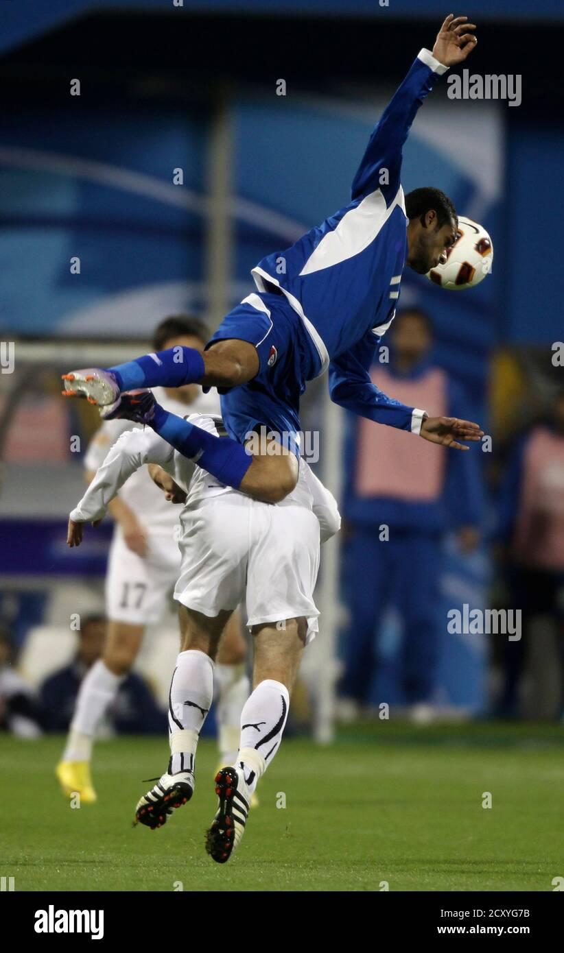 Kuwait's Bader Al Mutwa (top) jumps for a header against Uzbekistan's Alexander Geynrikh during their 2011 Asian Cup Group A soccer match at Al Gharafa stadium in Doha January 12, 2011.   REUTERS/Suhaib Salem (QATAR  - Tags: SPORT SOCCER) Stock Photo