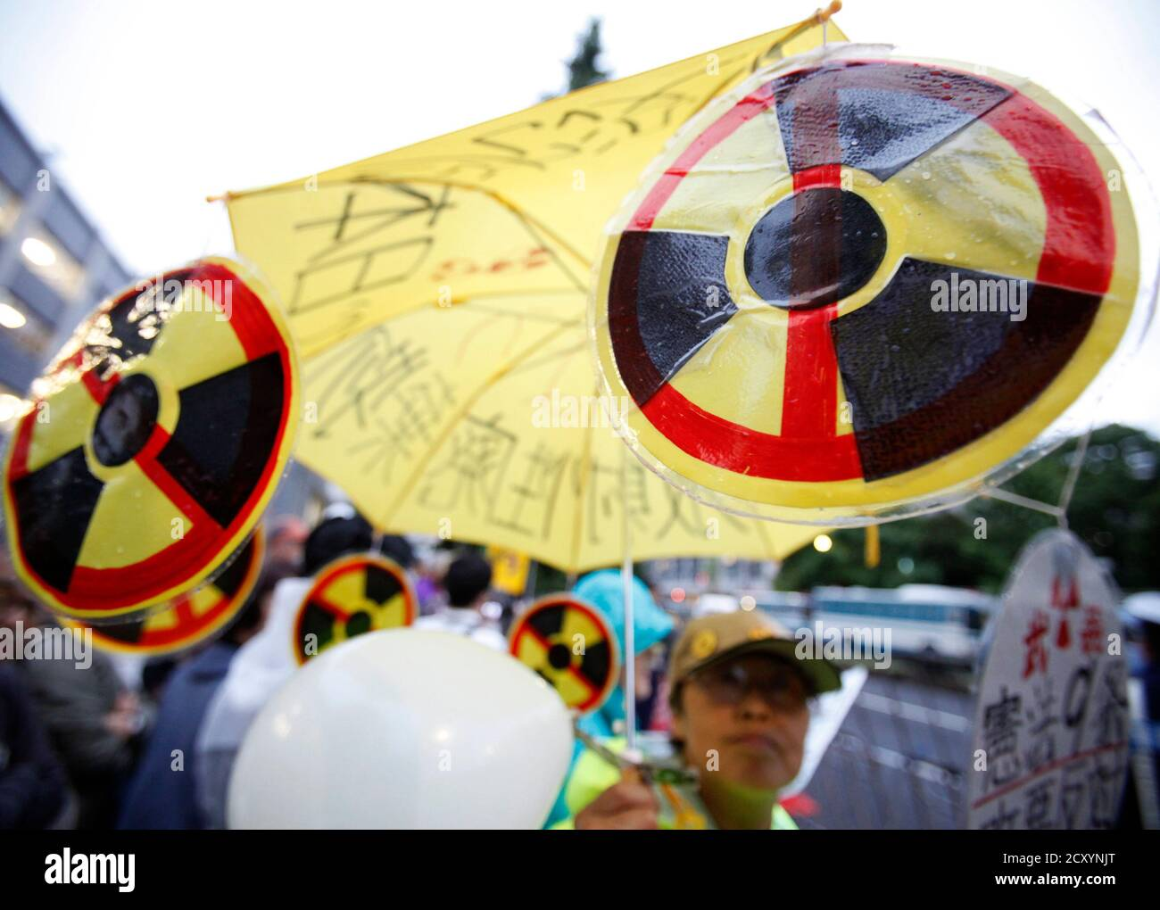 A woman holds an umbrella with illustrations of anti-nuclear signs during a demonstration outside the prime minister's official residence in Tokyo July 20, 2012. Japan's debate over nuclear power has become increasingly heated after incumbent Prime Minister Yoshihiko Noda's decision to restart idled reactors despite persistent public safety concerns following last year's Fukushima nuclear crisis. REUTERS/Yuriko Nakao (JAPAN - Tags: POLITICS CIVIL UNREST ENERGY) Stock Photo