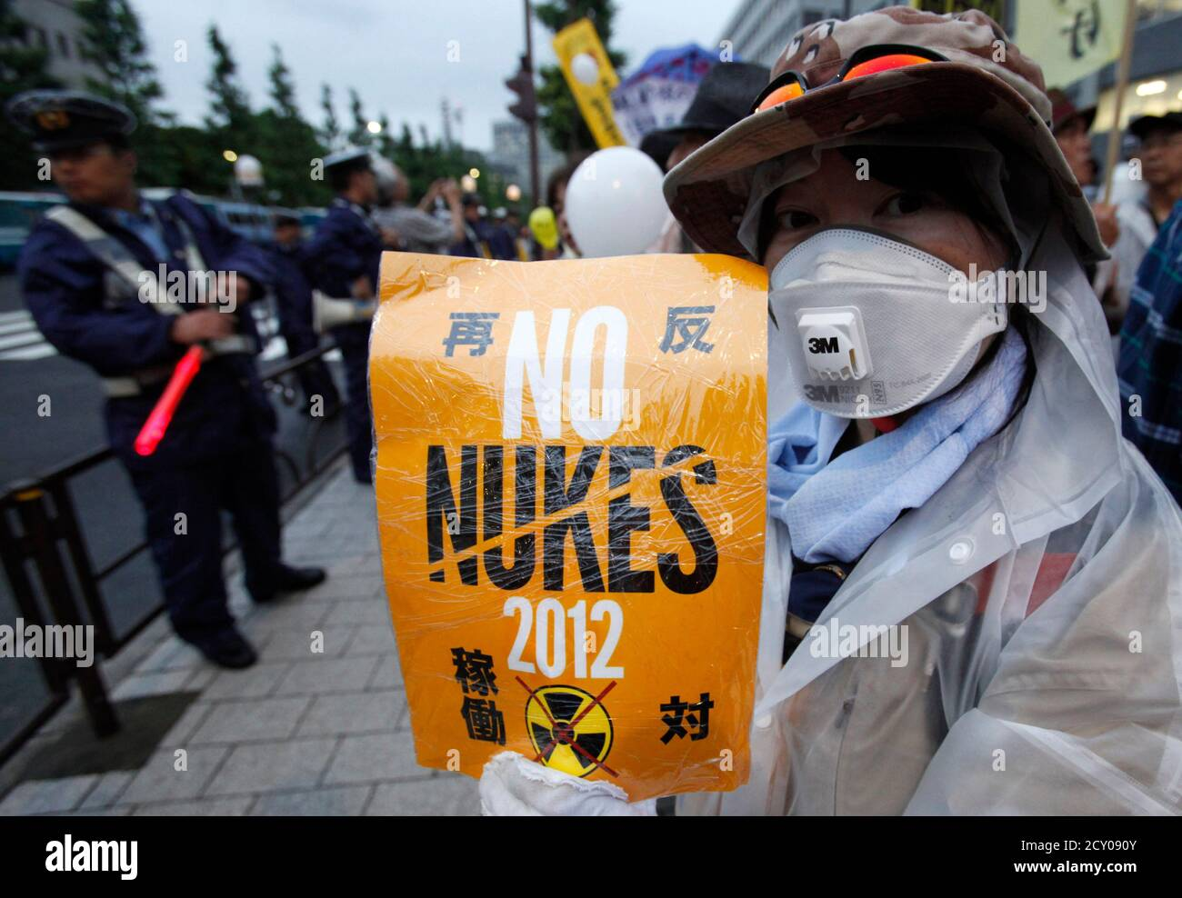 A woman wearing a mask takes part in an anti-nuclear demonstration outside prime minister's official residence in Tokyo July 20, 2012. Japan's debate over nuclear power has become increasingly heated after incumbent Prime Minister Yoshihiko Noda's decision to restart idled reactors despite persistent public safety concerns following last year's Fukushima nuclear crisis. REUTERS/Yuriko Nakao (JAPAN - Tags: POLITICS CIVIL UNREST ENERGY) Stock Photo