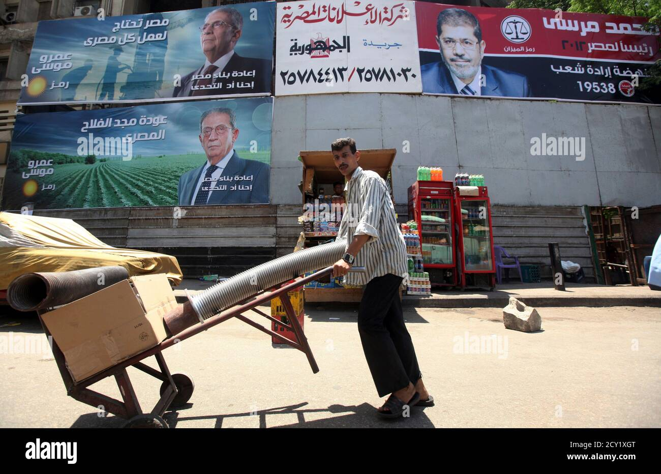 """A man walks under campaign election billboards of presidential candidate and former Arab League secretary general Amr Moussa (L) and presidential candidate and head of the Muslim Brotherhood Mohamed Mursi (R), in Cairo May 7, 2012. Voting starts on May 23-24 in the election to choose a new president after Hosni Mubarak was turfed out of office last year. The billboards read, """"Amr Moussa, we are up to the challenge,"""" (L) and """"president for Egypt."""" (R) REUTERS/Amr Abdallah Dalsh  (EGYPT - Tags: POLITICS ELECTIONS) Stock Photo"""