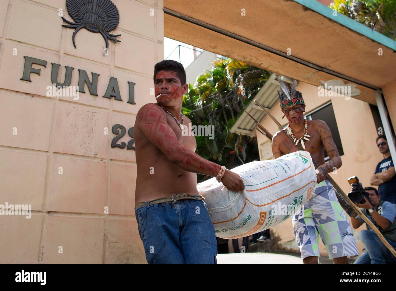 Amazon Indians of various tribes carry their belongings as they are expelled from the headquarters of Brazil's Indian affairs bureau FUNAI by police acting under court order, in Manaus January 29, 2014. Some 50 Indians have been occupying FUNAI's building since last November as they pressure the institution to change its current director, Eduardo Desiderio Chaves, who they complained for being a non-Indian and is accused of ignoring their needs, according to the group.   REUTERS/Bruno Kelly (BRAZIL - Tags: ENVIRONMENT POLITICS) Stock Photo