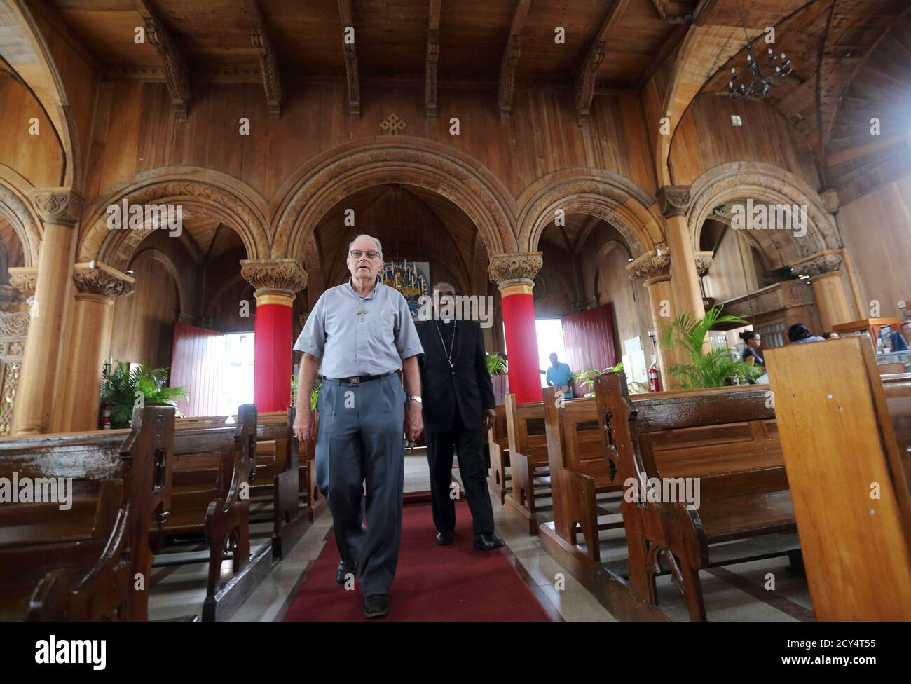 Suriname's Bishop Wim de Bekker (L) walks with Caribbean Cardinal Kelvin Felix inside the Roman Catholic St. Peter and Paul Cathedral, made entirely of wood, in Paramaribo, April 5, 2014. The cathedral, built between 1883 and 1885 of cedar and considered today the largest and tallest wooden structure in the Western Hemisphere, has interior carvings done by Maroons, runaway African slaves, after the abolition of slavery. The cathedral will be elevated to the category of Basilica Minore on April 6. REUTERS/Ranu Abhelakh (SURINAME - Tags: RELIGION) Stock Photo
