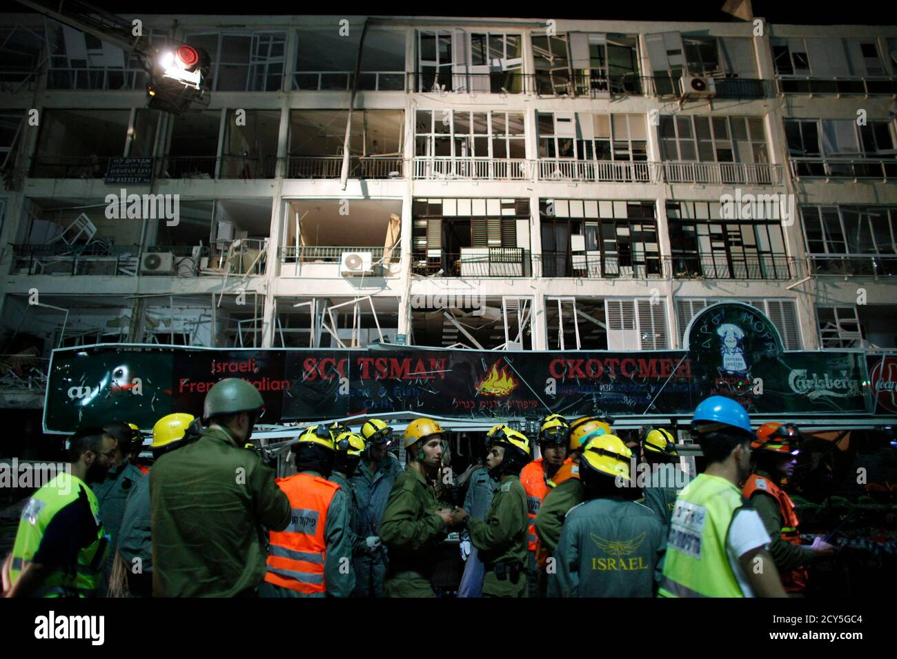 Rescue workers gather next to a damaged building at the scene of an explosion in the coastal Israeli city of Netanya June 17, 2011. A huge blast caused by a gas leak killed three people in Netanya early on Friday, police said. At least 15 other people were injured in the explosion, which caused the first floor of a four-story residential building to collapse. Local media said earlier that many people were trapped, but emergency services said everyone had been removed from the building. REUTERS/Nir Elias (ISRAEL - Tags: DISASTER) Stock Photo