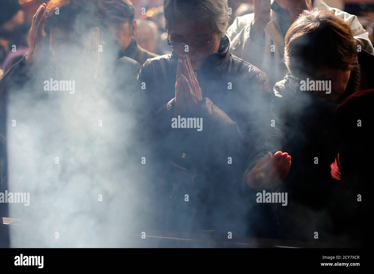 People burn incense as they offer prayers at a temple in Tokyo's Sugamo district, an area popular among the Japanese elderly, in Tokyo January 14, 2015. Japanese Prime Minister Shinzo Abe's cabinet approved on Wednesday a record $812 billion budget for the coming fiscal year while cutting new borrowing for a third straight year in a bid to balance growth and fiscal reform. The largest budget item, social welfare spending, will rise 1 trillion yen to a record 31.53 trillion yen.  REUTERS/Toru Hanai (JAPAN - Tags: SOCIETY BUSINESS POLITICS RELIGION) Stock Photo