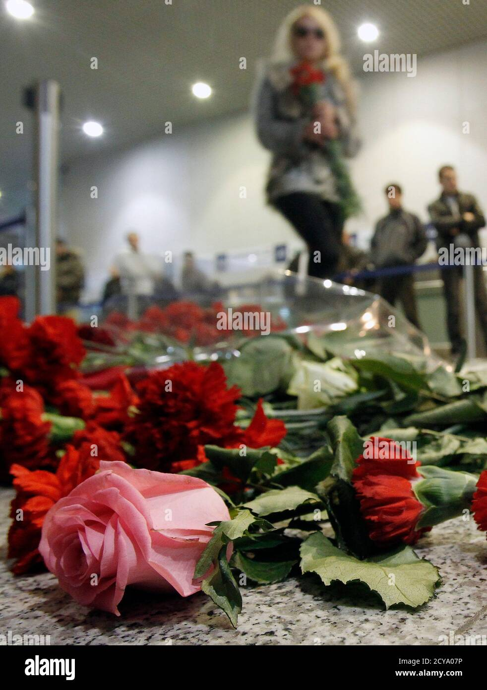 A woman stands next to the flowers left on a floor in memory of those killed in Monday's blast at Moscow's Domodedovo airport January 25, 2011. Russia's President Dmitry Medvedev ordered investigators on Tuesday to root out the culprits behind a deadly bombing at Russia's busiest airport and threatened sackings over security lapses he said had aided the attack. REUTERS/Denis Sinyakov (RUSSIA - Tags: CRIME LAW TRANSPORT) Stock Photo