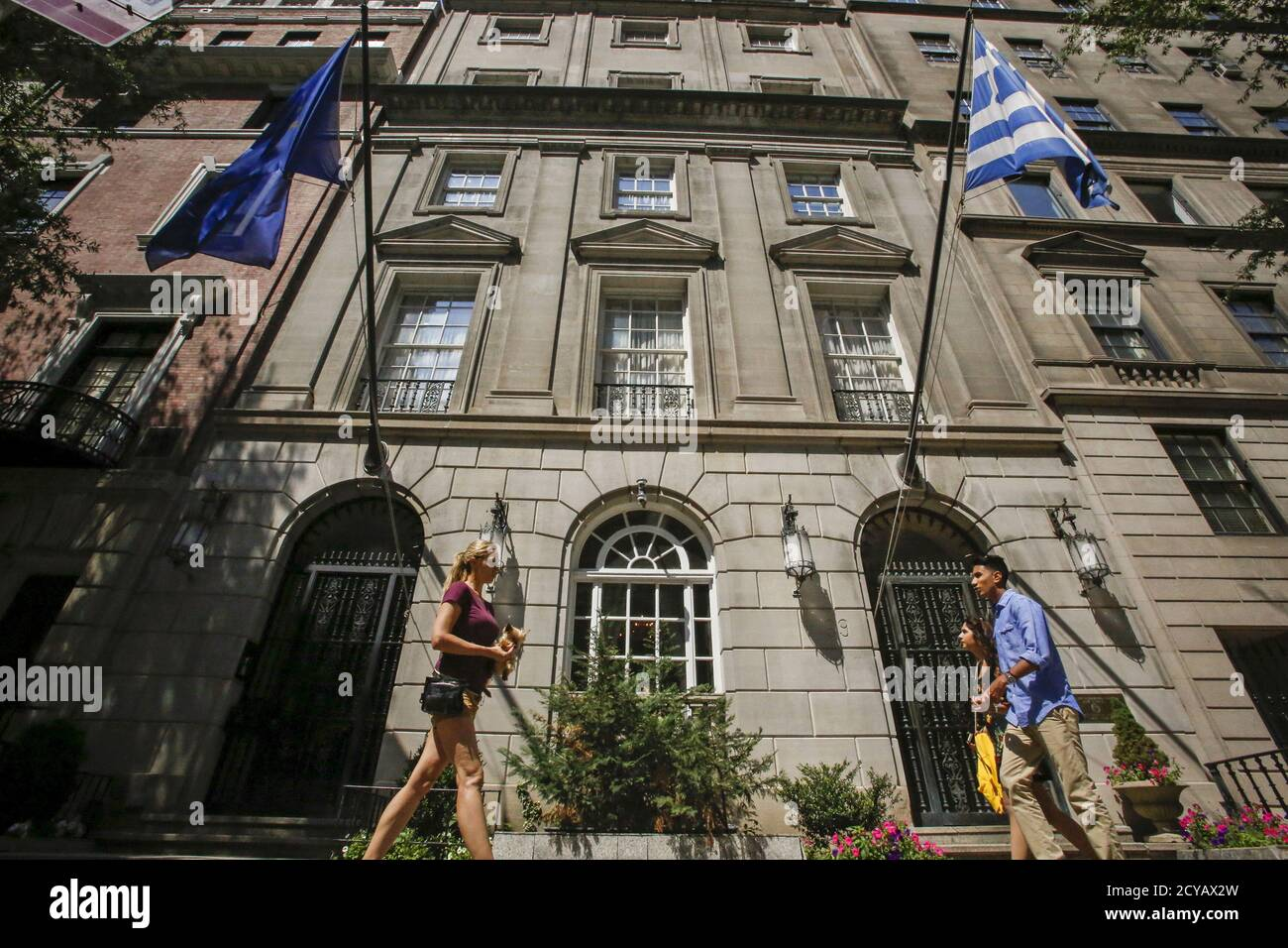 The flags of the European Union and Greece flutter as people walk in front of the Greece consulate in New York June 30, 2015. REUTERS/Eduardo Munoz Stock Photo