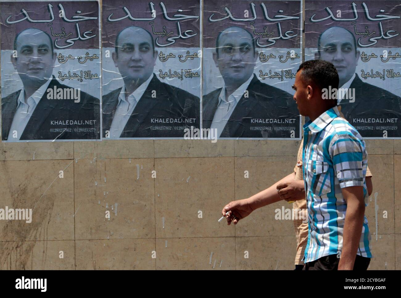 Men walk past campaign posters of presidential candidate and lawyer and rights activist Khaled Ali in Cairo May 7, 2012. Voting starts on May 23-24 in the election to choose a new president after Hosni Mubarak was turfed out of office last year. REUTERS/Amr Abdallah Dalsh  (EGYPT - Tags: POLITICS ELECTIONS) Stock Photo