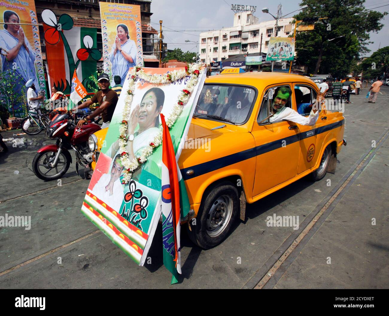 A man drives an iconic yellow ambassador taxi with a portrait of Trinamool Congress party leader Mamata Banerjee attached to the front in a street in Kolkata, May 13, 2011. India's ruling Congress-led coalition overturned three decades of communist rule in the swing state of West Bengal on Friday, one of several regional poll victories that could give some respite for a beleaguered Prime Minister Manmohan Singh. The Congress alliance led by maverick populist Mamata Banerjee was leading in 215 seats out of the 294 at stake in the West Bengal state assembly, with the communists ahead in 72 seats Stock Photo