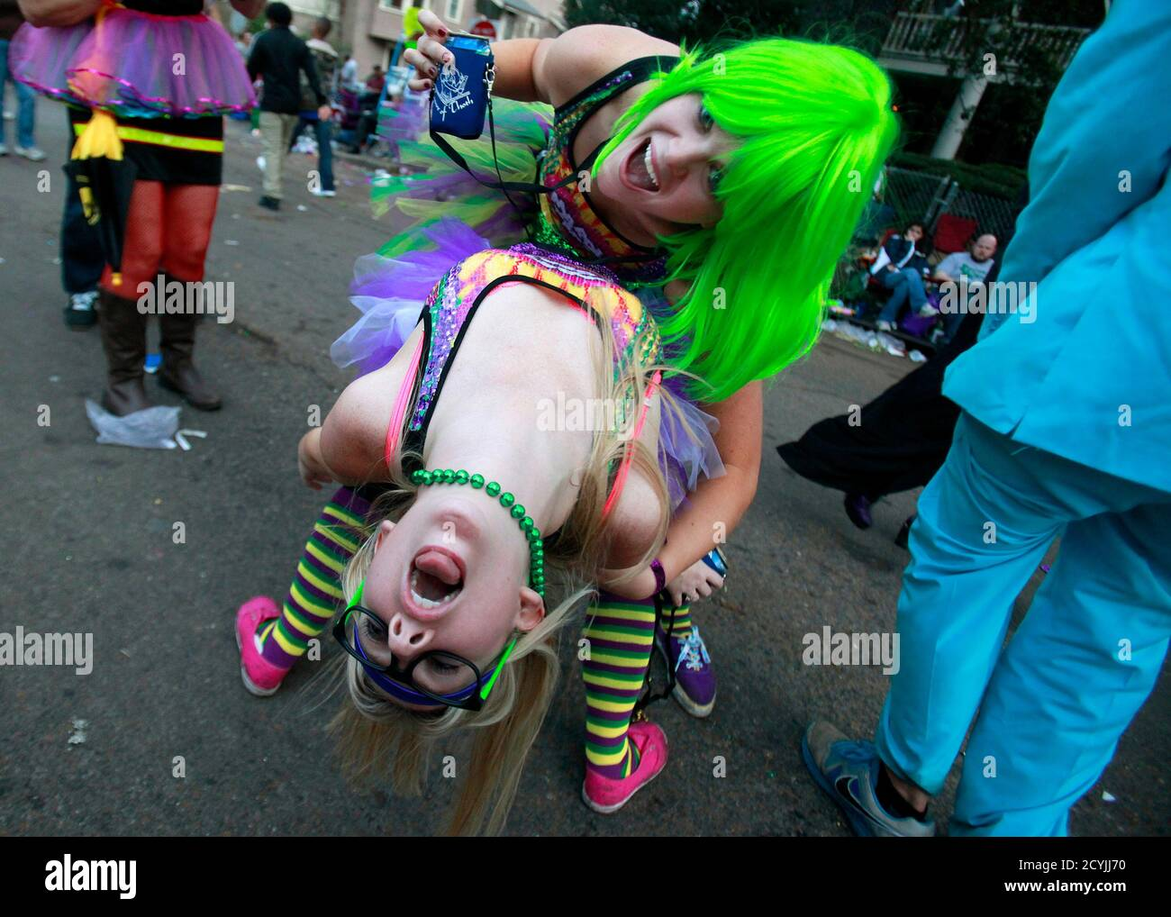 Lauren Whiddon (bottom) and Mari Wisdom dance on St. Charles Avenue as they wait for the Krewe of Bacchus parade in New Orleans, Louisiana February 10, 2013. Mardi Gras day will be celebrated on February 12, 2013. REUTERS/Sean Gardner (UNITED STATES - Tags: SOCIETY) Stock Photo