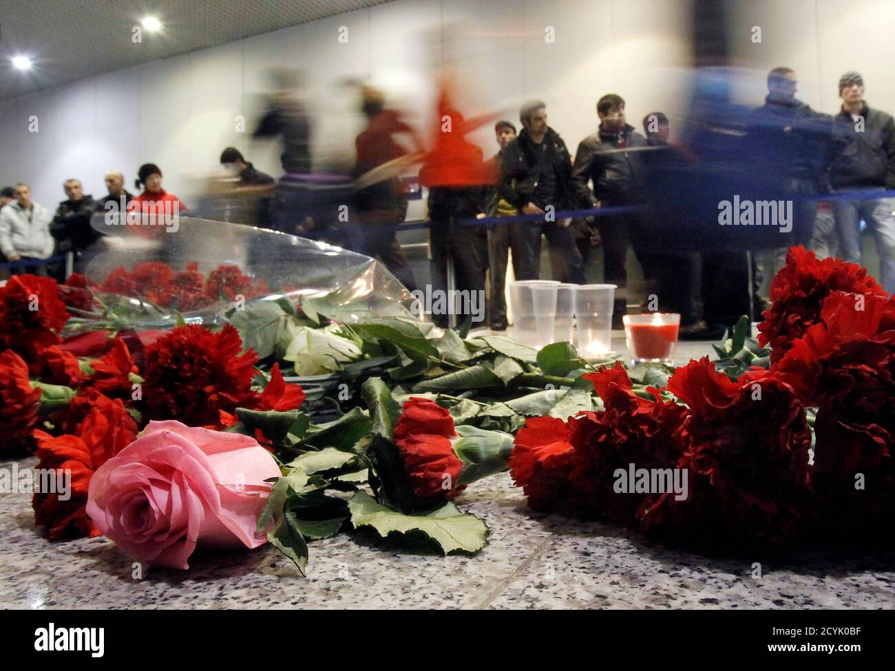 People walk past flowers left on a floor in memory of those killed in Monday's blast at Moscow's Domodedovo airport January 25, 2011. Russia's President Dmitry Medvedev ordered investigators on Tuesday to root out the culprits behind a deadly bombing at Russia's busiest airport and threatened sackings over security lapses he said had aided the attack. REUTERS/Denis Sinyakov (RUSSIA - Tags: CRIME LAW TRANSPORT IMAGES OF THE DAY) Stock Photo