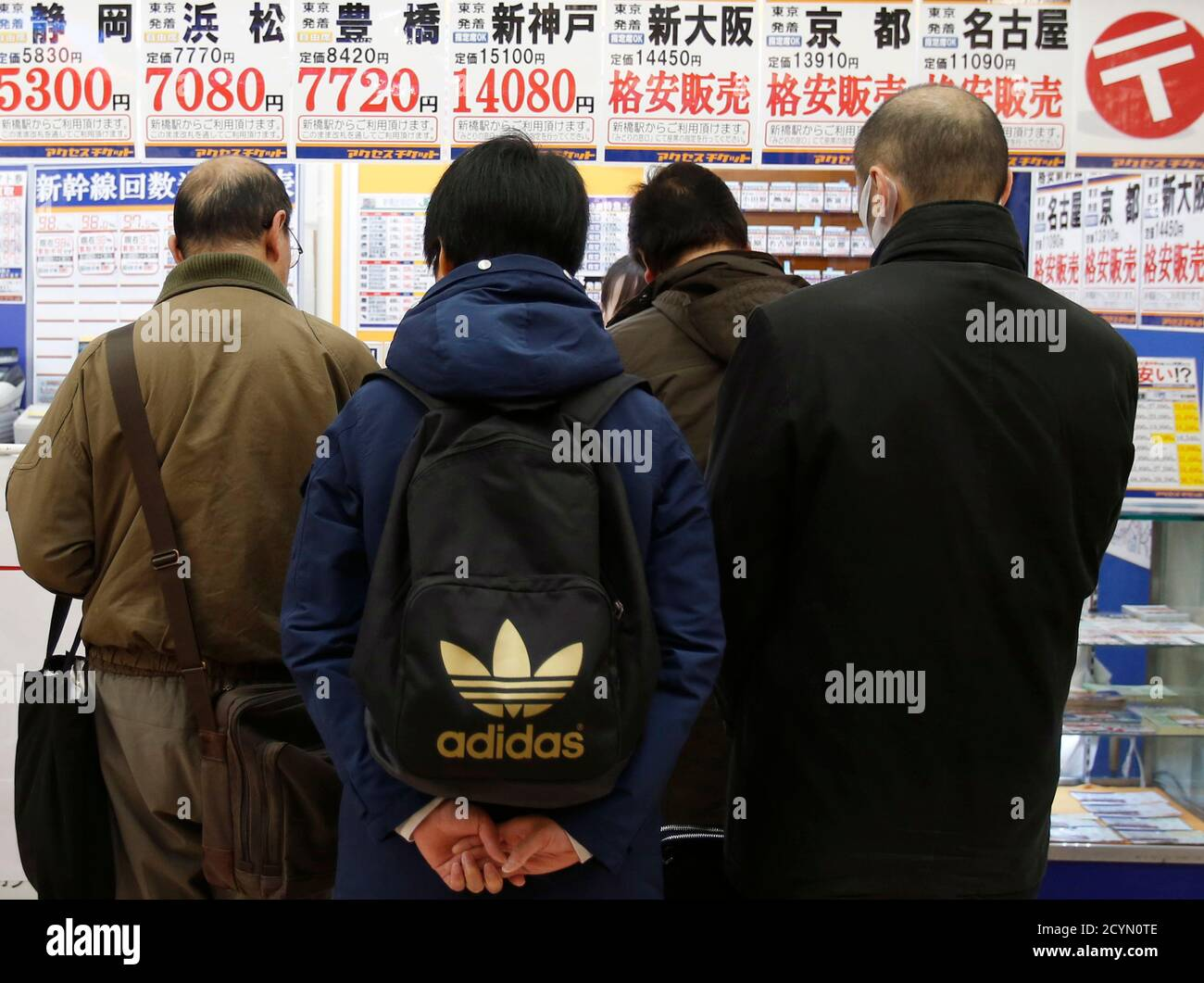 People look at prices at a discount ticket shop in Tokyo January 14, 2015. Japanese Prime Minister Shinzo Abe's cabinet approved on Wednesday a record $812 billion budget for the fiscal year starting on April 1, while cutting new borrowing for a third straight year in a bid to balance growth and fiscal reform. The largest budget item, social welfare spending, will rise 1 trillion yen to a record 31.53 trillion yen. REUTERS/Yuya Shino (JAPAN - Tags: BUSINESS SOCIETY POLITICS) Stock Photo