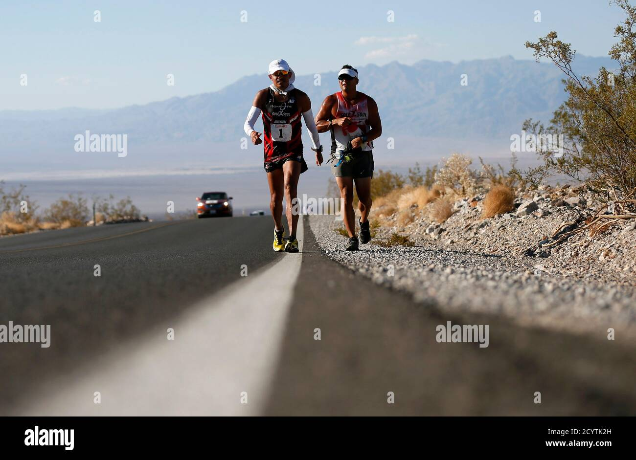 Oswaldo Lopez of Mexico, 41, (L) competes in the Badwater Ultramarathon in Death Valley National Park, California July 15, 2013. The 135-mile (217 km) race, which bills itself as the world's toughest foot race, goes from Death Valley to Mt. Whitney, California in temperatures which can reach 130 degrees Fahrenheit (55 Celsius).  REUTERS/Lucy Nicholson (UNITED STATES - Tags: SPORT ATHLETICS ENVIRONMENT) Stock Photo