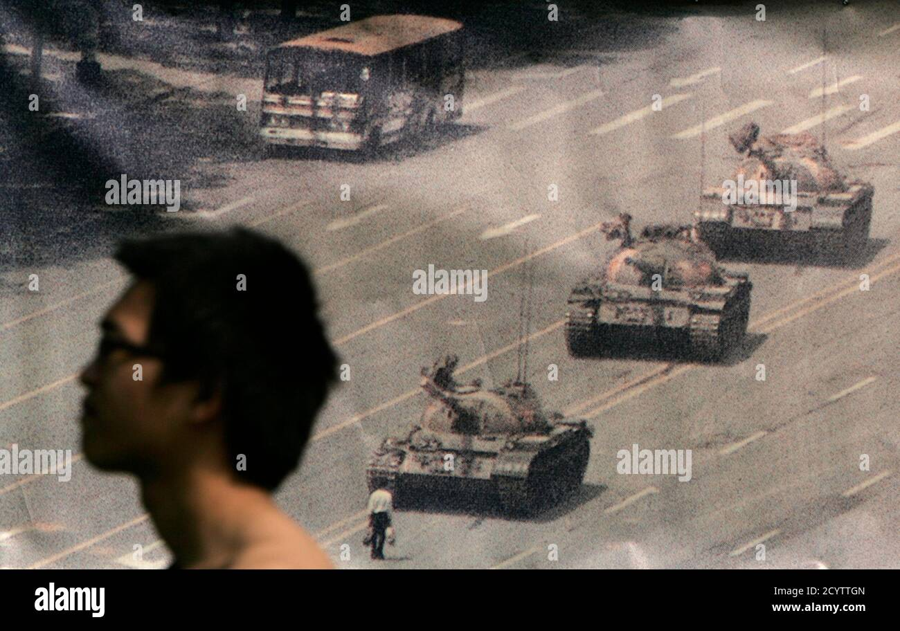 A man walks past a banner, printed with a photo of a man standing in front of tanks during the 1989 military crackdown on pro-democracy protesters around Beijing's Tiananmen Square, at Hong Kong's Victoria Park June 4, 2009. Tens of thousands of people are expected to attend a candlelight vigil later in the evening to commemorate those who died in the crackdown. REUTERS/Tyrone Siu (CHINA ANNIVERSARY CONFLICT POLITICS) Stock Photo
