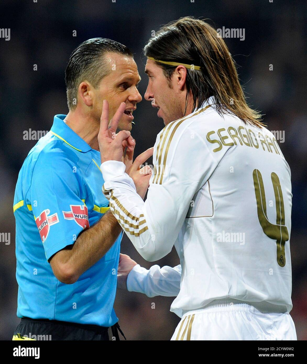 "Real Madrid's Sergio Ramos argues with referee Cesar Muniz (L) during their Spanish King's Cup quarter-final first leg ""El Clasico"" soccer match against Barcelona at the Santiago Bernabeu stadium in Madrid January 18, 2012.    REUTERS/Felix Ordonez (SPAIN - Tags: SPORT SOCCER) Stock Photo"