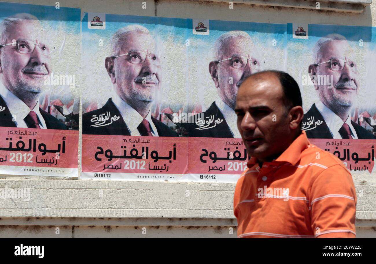A man walks past campaign posters of presidential candidate and former leader of the Muslim Brotherhood Dr. Abdel Moneim Abu El Fotouh in Cairo May 7, 2012. Voting starts on May 23-24 in the election to choose a new president after Hosni Mubarak was turfed out of office last year. REUTERS/Amr Abdallah Dalsh  (EGYPT - Tags: POLITICS ELECTIONS) Stock Photo