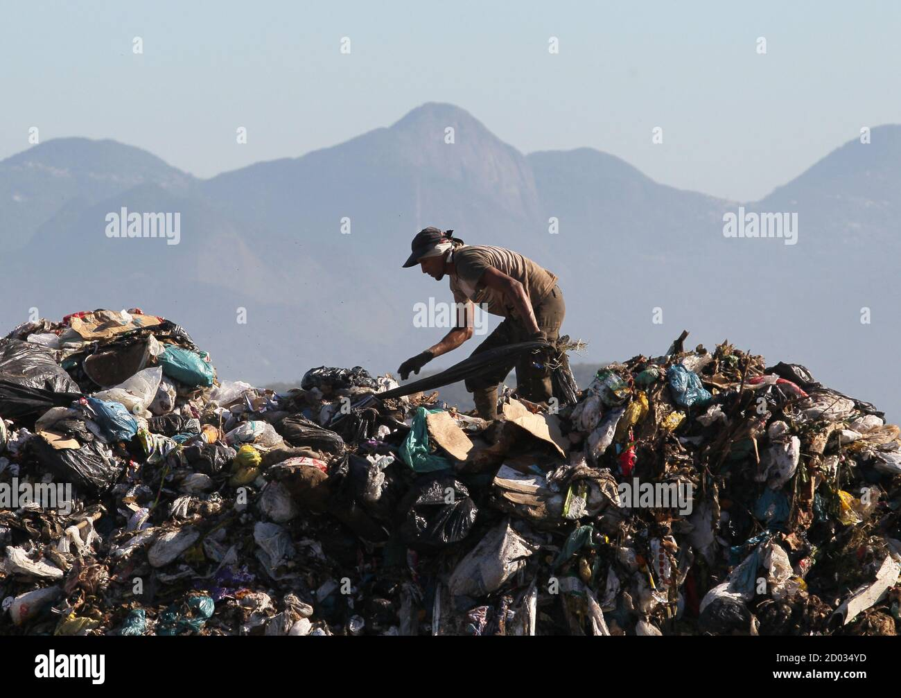 """A man collects recyclable materials from Jardim Gramacho landfill, where the documentary """"Lixo Extraordinario"""" (Waste Land) was filmed, in Rio de Janeiro January 28, 2011. Waste Land follows artist Vik Muniz on a journey from his home in Brooklyn to his native Brazil, where he met a band of garbage pickers in the world's largest garbage dump, Jardim Gramacho. Waste Land has been nominated for an Oscar in the category of Best Documentary. REUTERS/Sergio Moraes (BRAZIL - Tags: ENVIRONMENT SOCIETY) Stock Photo"""