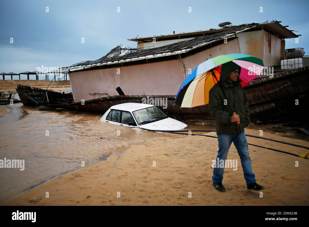 A man walks next to a car and a beach restaurant that sank into the sand following heavy rains and flooding on a beach of the Mediterranean sea near Kibbutz Nitzanim in southern Israel December 14, 2013. REUTERS/Amir Cohen (ISRAEL - Tags: ENVIRONMENT TPX IMAGES OF THE DAY) Stock Photo
