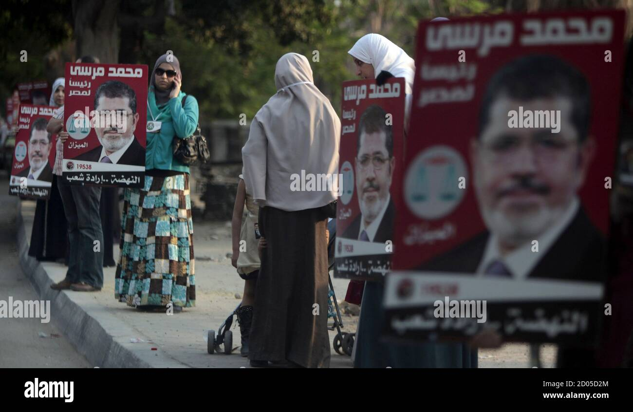 """Supporters of Mohamed Mursi, the head of the Muslim Brotherhood's political party and the Brotherhood's presidential candidate, hold posters of Mursi during a human chain with the participation of party members and supporters of the campaign for the presidency, which extended over a distance of 40km (25 miles) at """"Kornish El Nile"""" in Cairo May 10, 2012. Voting starts on May 23-24 in the election to choose a new president after Hosni Mubarak was turfed out of office last year.   REUTERS/Amr Abdallah Dalsh  (EGYPT - Tags: POLITICS ELECTIONS) Stock Photo"""