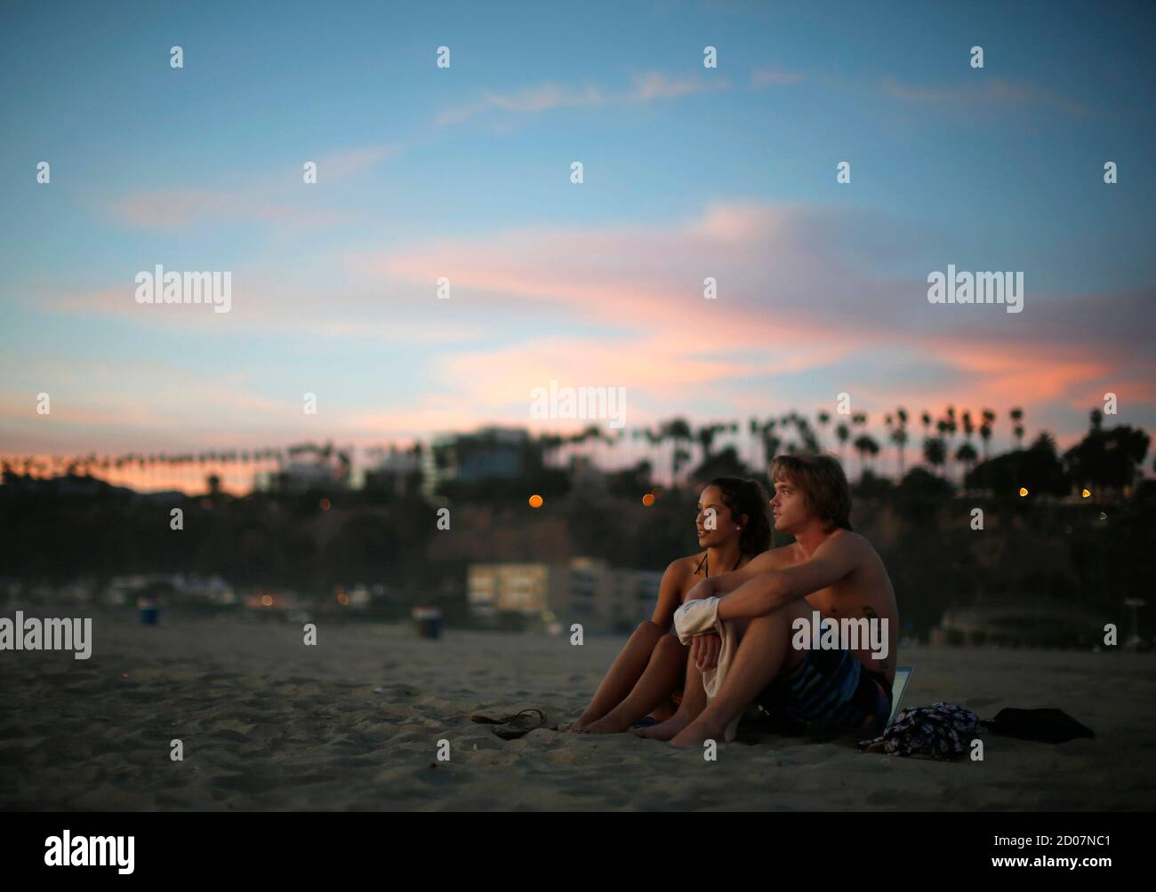 Chris Truebe (R), 27, and Kara Ortega, 20, watch the sun set over the Pacific Ocean on the beach in Santa Monica, California October 3, 2014. Southern California sizzled in a heat wave as temperatures soared above 100 degrees Fahrenheit in parts of Los Angeles.  REUTERS/Lucy Nicholson (UNITED STATES - Tags: ENVIRONMENT SOCIETY) Stock Photo