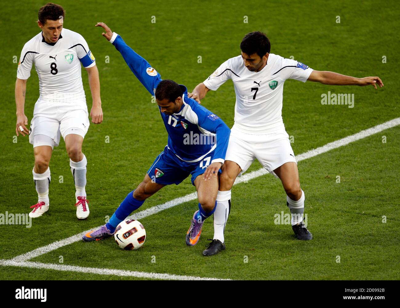 Uzbekistan's Azizbek Haydarov (R) challenges Kuwait's Bader Al Mutwa (C) while teammate Server Djeparov looks on during their 2011 Asian Cup Group A soccer match at Al Gharafa stadium in Doha January 12, 2011. REUTERS/Oleg Popov (QATAR  - Tags: SPORT SOCCER) Stock Photo