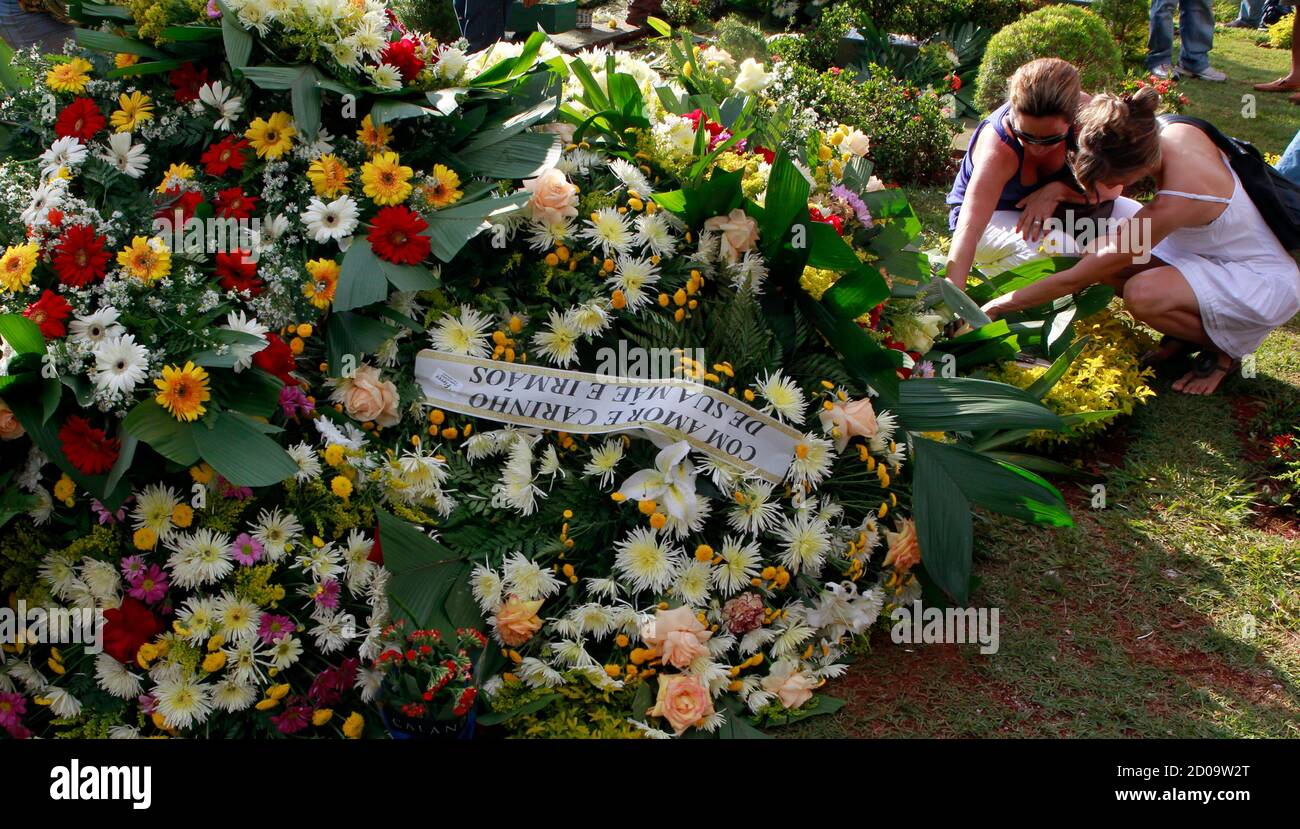 Women place flowers on the grave of Brazil's 1982 World Cup captain Socrates during his funeral ceremony in Ribeirao Preto December 4, 2011. Socrates, the 'Golden Heel' renowned as one of the great playmakers of his generation, died in hospital on Sunday of septic shock at the age of 57, his doctors said in a statement.   REUTERS/Paulo Whitaker  (BRAZIL - Tags: SPORT SOCCER OBITUARY) Stock Photo
