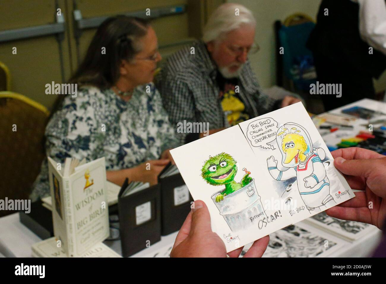 A man displays sketches by Caroll Spinney (back R) as he signs autographs during the Dean Martin Expo and Nostalgic, Comedy and Comic Convention featuring collection of memorabilia from the 1950's and 60's, in New York June 28, 2014. REUTERS/Eduardo Munoz (UNITED STATES - Tags: ENTERTAINMENT SOCIETY) Stock Photo