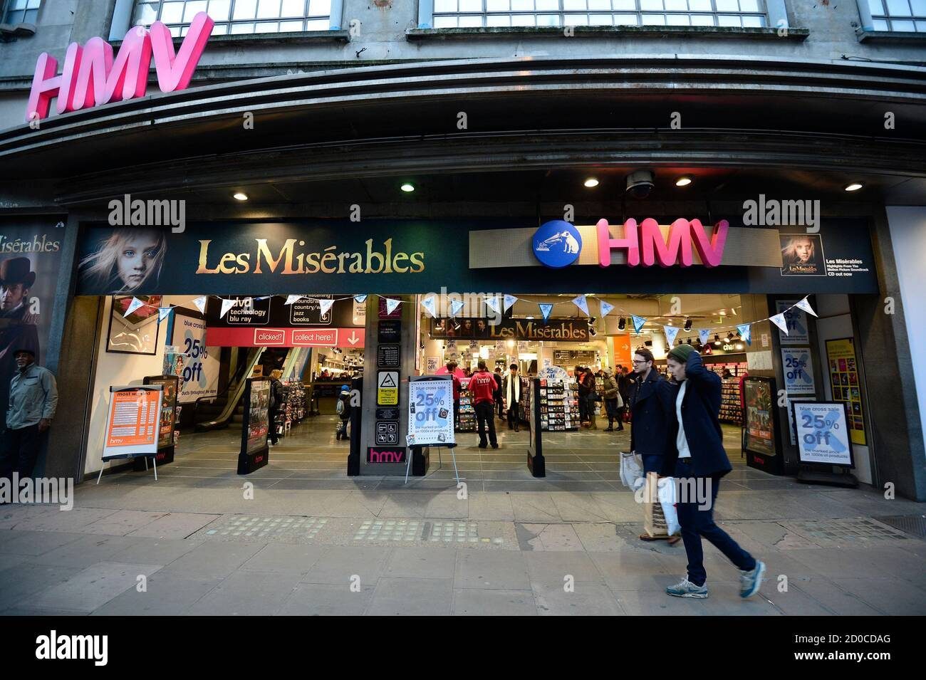 Shoppers pass an HMV shop in central London, January 15, 2013. HMV, the 92-year-old British music retailer seeking protection from creditors, is unlikely to have much of a future beyond a rump of stores and the internet, if other recent retail failures are any guide.   REUTERS/Paul Hackett (BRITAIN - Tags: BUSINESS ENTERTAINMENT) Stock Photo