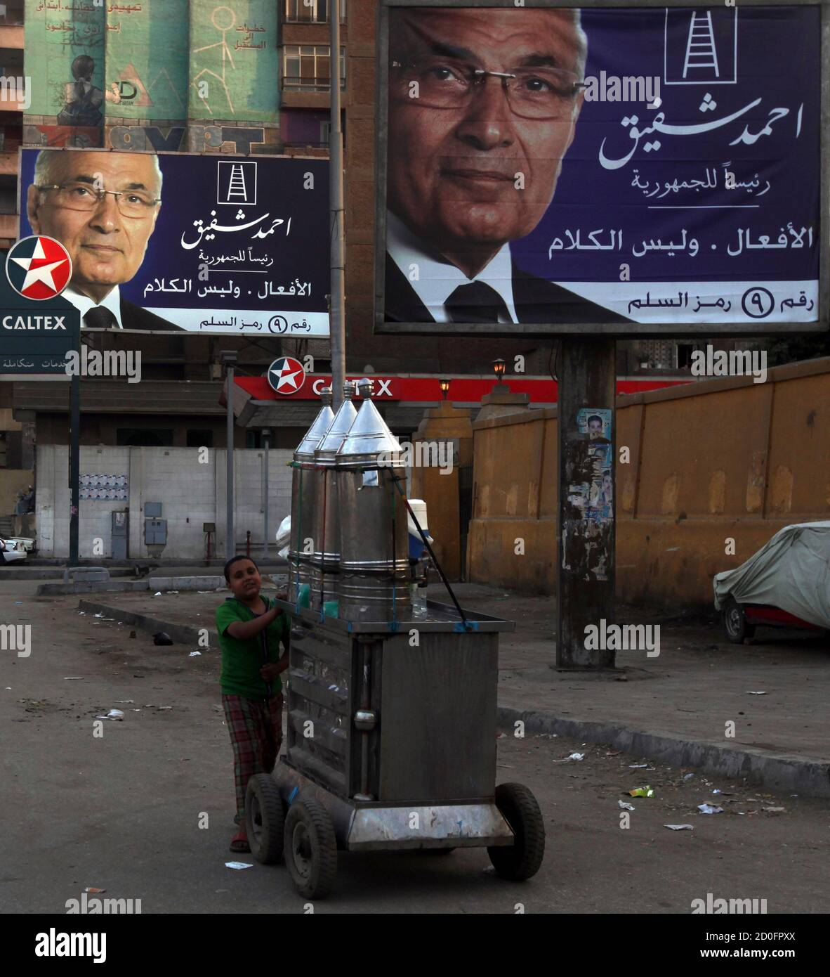 A street vendor walks under campaign election billboards of presidential candidate and former prime minister Ahmed Shafiq in Cairo May 7, 2012. Voting starts on May 23-24 in the election to choose a new president after Hosni Mubarak was turfed out of office last year. REUTERS/Amr Abdallah Dalsh  (EGYPT - Tags: POLITICS ELECTIONS) Stock Photo