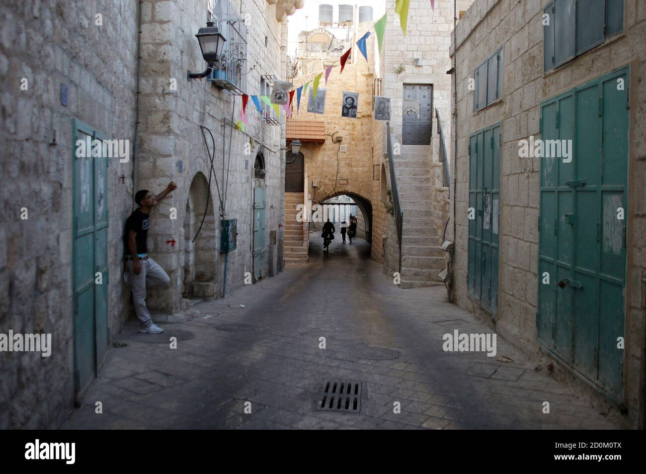 A Palestinian stands on a section of the Pilgrimage Route, the path which tradition says Joseph and Mary took into the West Bank city of Bethlehem in their trek from Nazareth some 2,000 years ago, June 28, 2012. Palestinians hope to persuade UNESCO this weekend to declare parts of Bethlehem, including the Pilgrimage Route, and its Church of the Nativity endangered World Heritage sites in order to expedite funding for repairs. REUTERS/Ammar Awad (WEST BANK - Tags: POLITICS RELIGION) Stock Photo