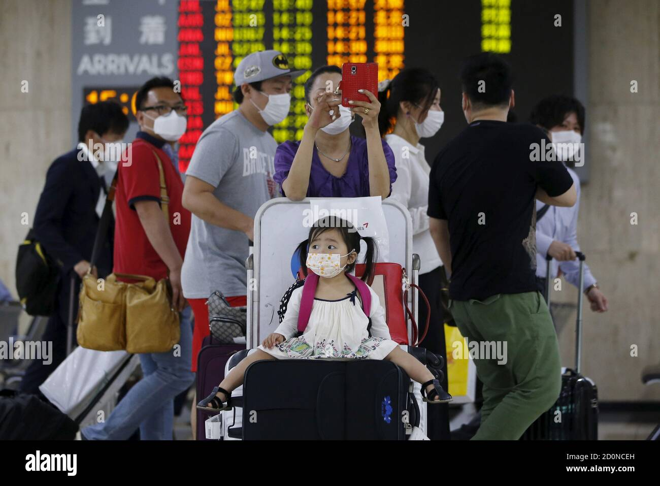A girl wearing a mask to prevent contracting Middle East Respiratory Syndrome (MERS) sits on a luggage as others walk past them at Gimpo International Airport in Seoul, South Korea, June 17, 2015. South Korea on Wednesday reported eight new cases of MERS, whilst another person infected with the virus died, health officials said, bringing to 20 the number of fatalities in the outbreak that began last month.   REUTERS/Kim Hong-Ji Stock Photo