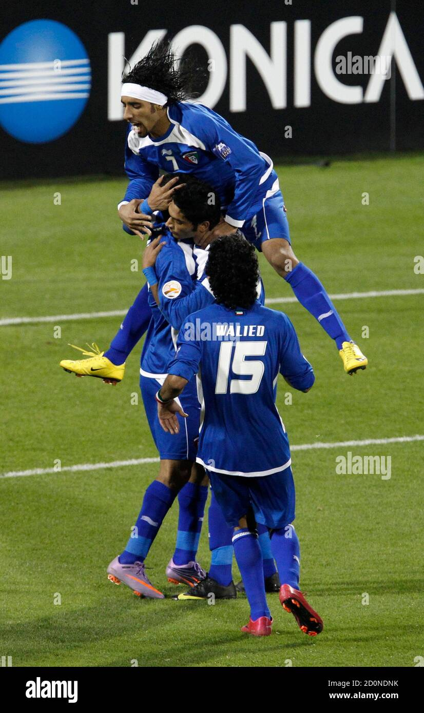 Kuwait's Bader Al Mutwa (L) is congratulated by his teammates after scoring a penalty against Uzbekistan during their 2011 Asian Cup Group A soccer match at Al Gharafa stadium in Doha January 12, 2011.     REUTERS/Oleg Popov (QATAR  - Tags: SPORT SOCCER) Stock Photo