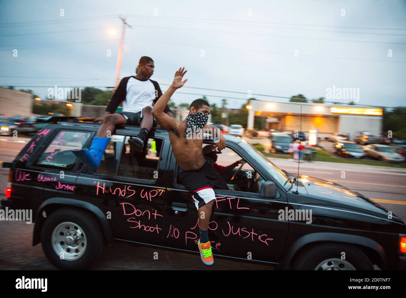 Protesters hang out of a car as they honk their horn and chant during ongoing demonstrations in reaction to the shooting of Michael Brown in Ferguson, Missouri August 16, 2014. Missouri Governor Jay Nixon declared a state of emergency and imposed a curfew in Ferguson on Saturday following a week-long series of racially charged protests and looting over the shooting of the unarmed black teenager by a white police officer. REUTERS/Lucas Jackson (UNITED STATES - Tags: CIVIL UNREST CRIME LAW POLITICS TPX IMAGES OF THE DAY) Stock Photo