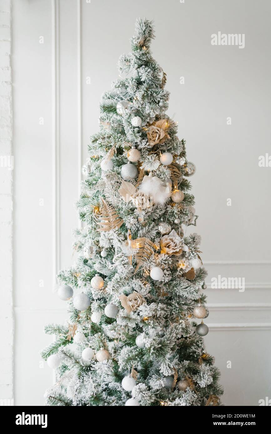 Christmas Tree With White Silver And Gold Toys On A White Classic Wall Background Stock Photo Alamy